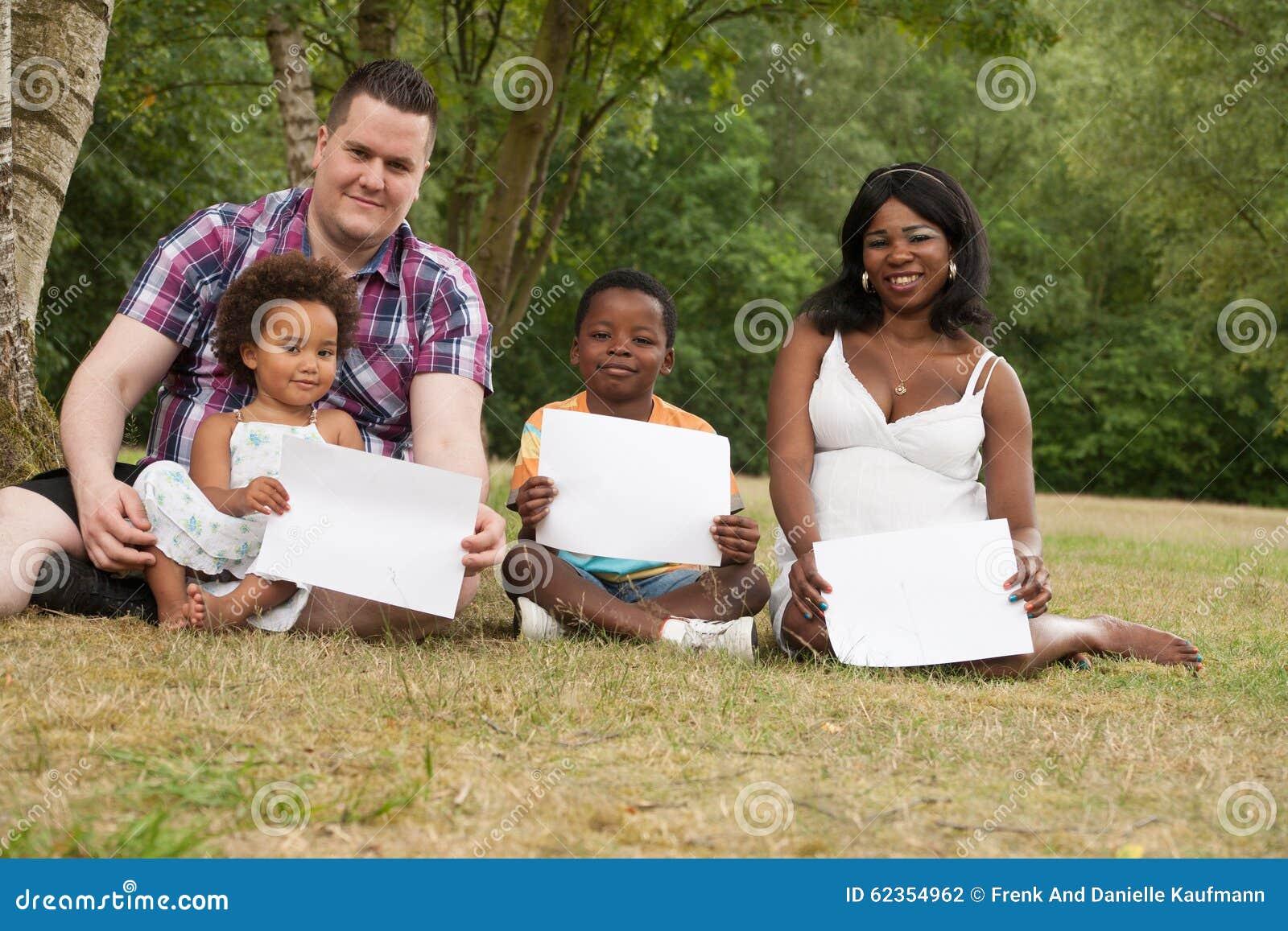 Πολυπολιτισμική οικογένεια με τους κενούς πίνακες