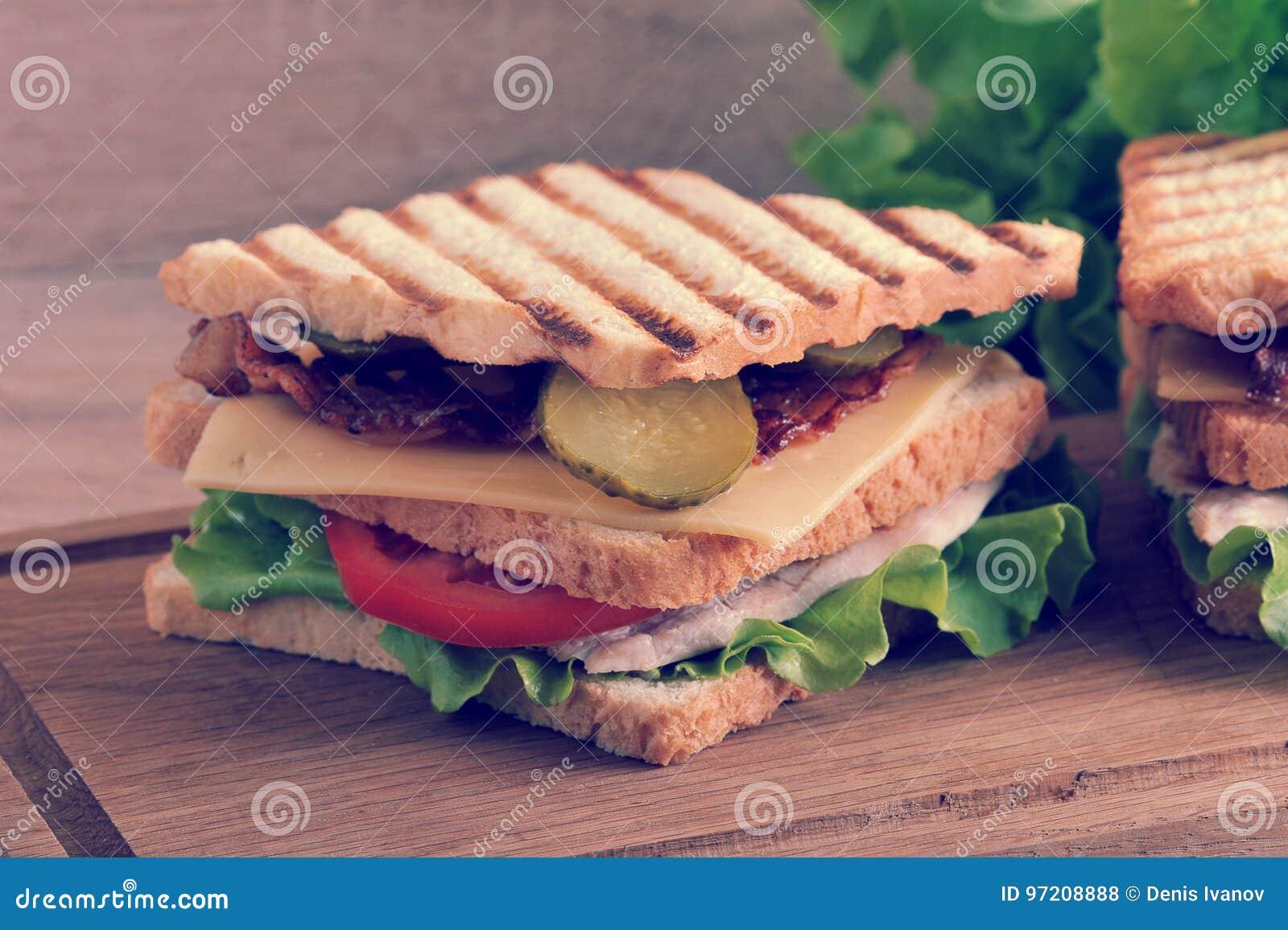 Πολυστρωματικό σάντουιτς με το τυρί, το ζαμπόν, τις ντομάτες, τα τουρσιά και το LE