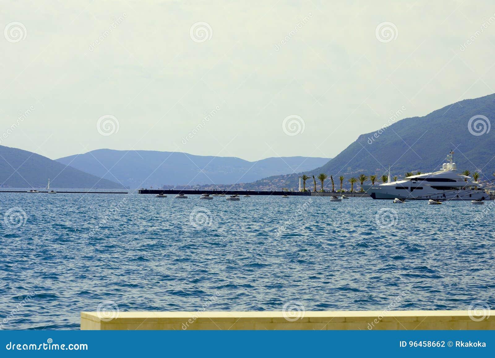 Πολυτελής βάρκα που δένεται σε έναν όμορφο κόλπο που περιβάλλεται από το mounta