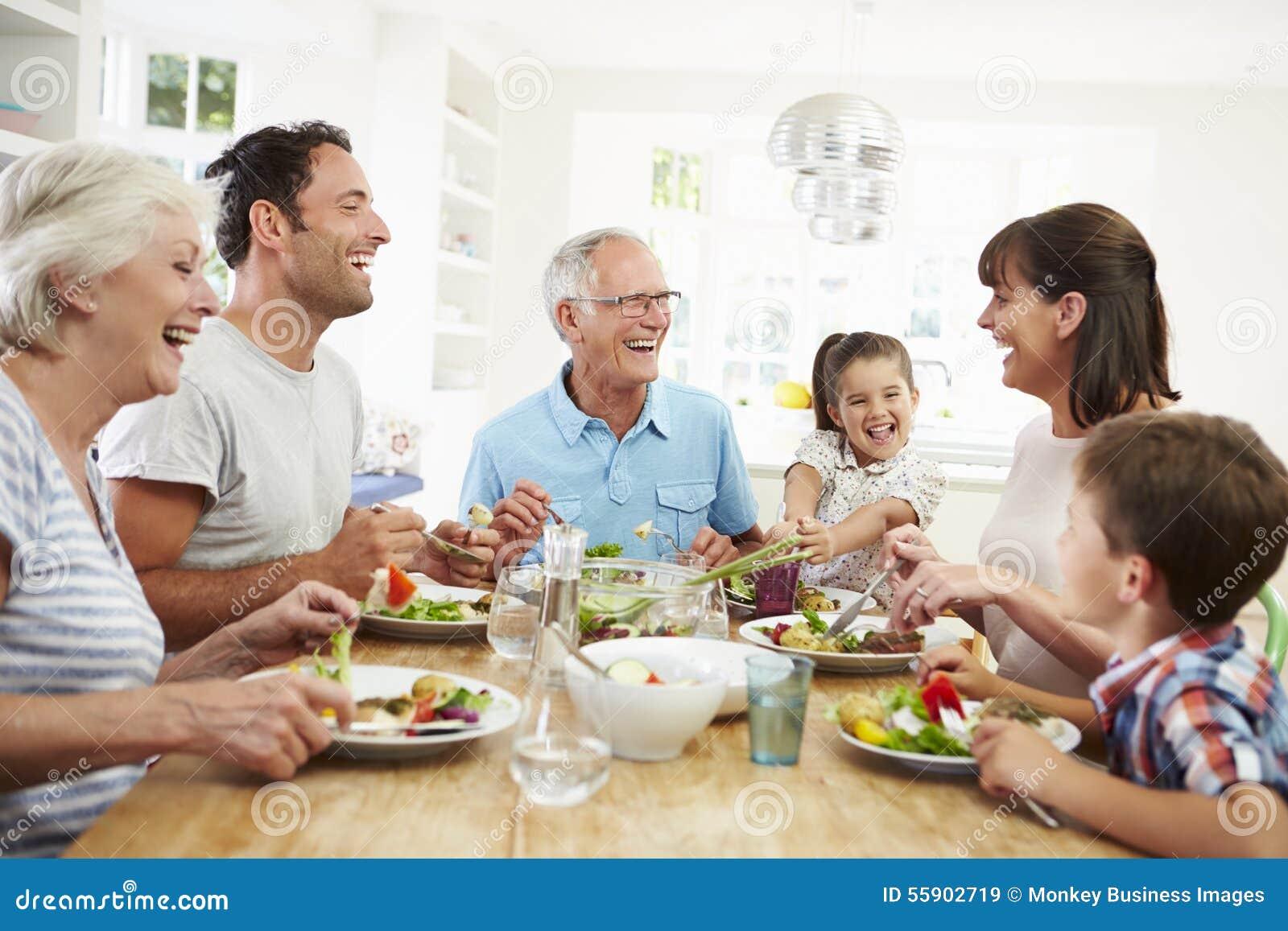Πολυ οικογένεια παραγωγής που τρώει το γεύμα γύρω από τον πίνακα κουζινών
