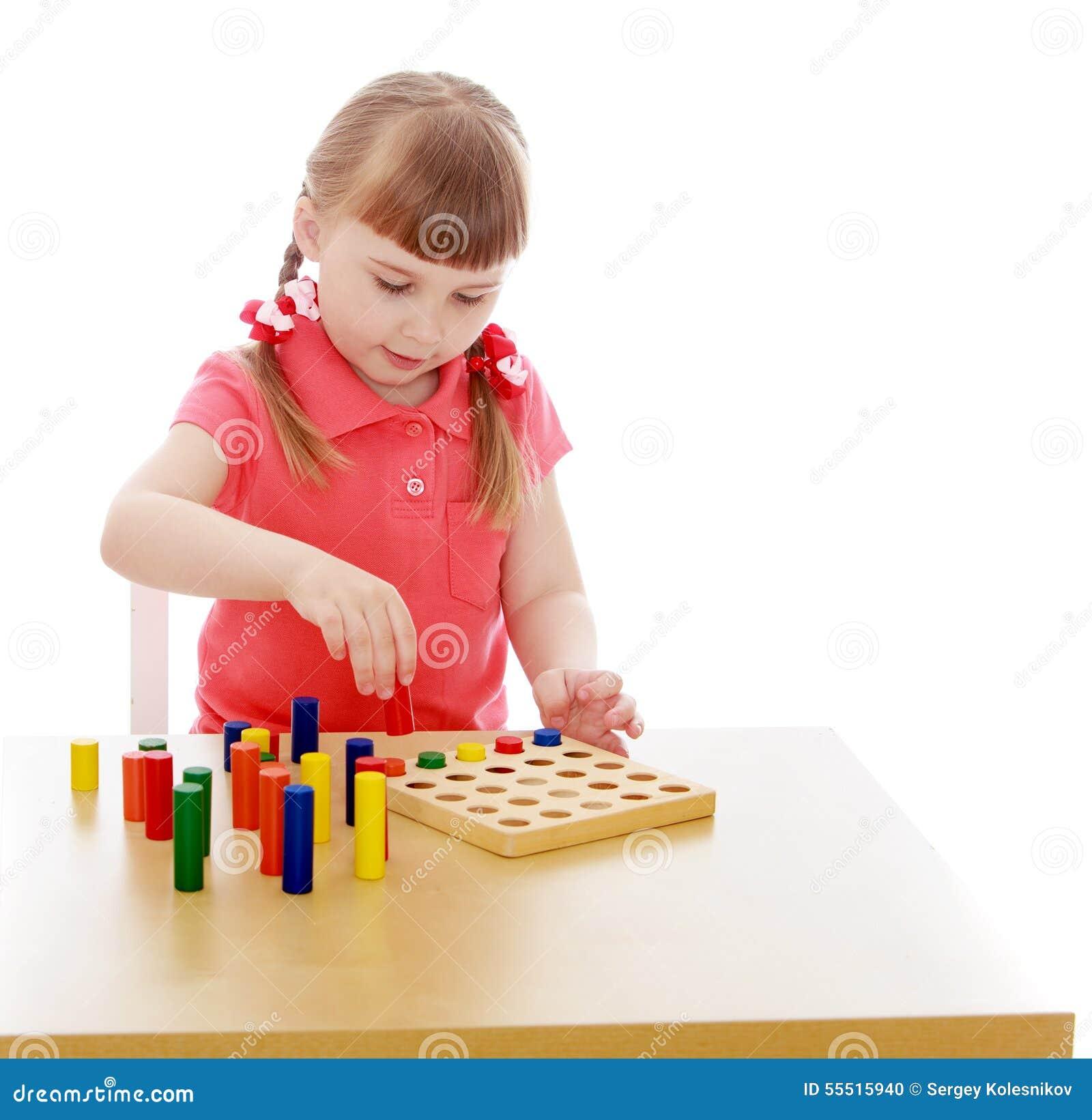 960b58d56975 Πολύ έξυπνο κορίτσι ξανθό στο παιχνίδι παιδικών σταθμών Montessori στα  υλικά Montessori που κάθονται πίνακας-απομονωμένη στο άσπρο υπόβαθρο