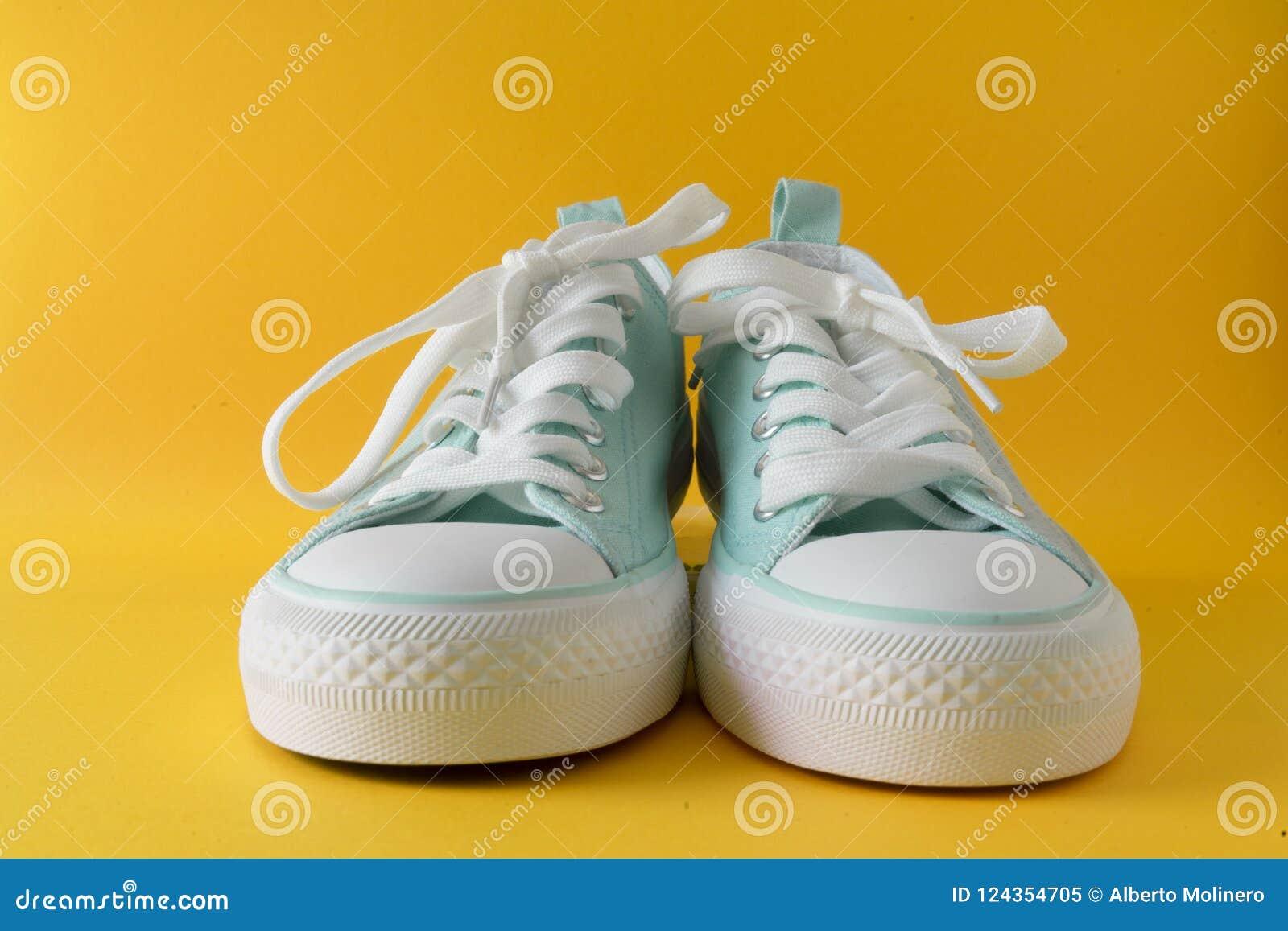 938bb6189e5 Ένα ζευγάρι των πάνινων παπουτσιών σε ένα κίτρινο υπόβαθρο Λαϊκά χρώματα  και ένα σύγχρονο ζευγάρι των παπουτσιών