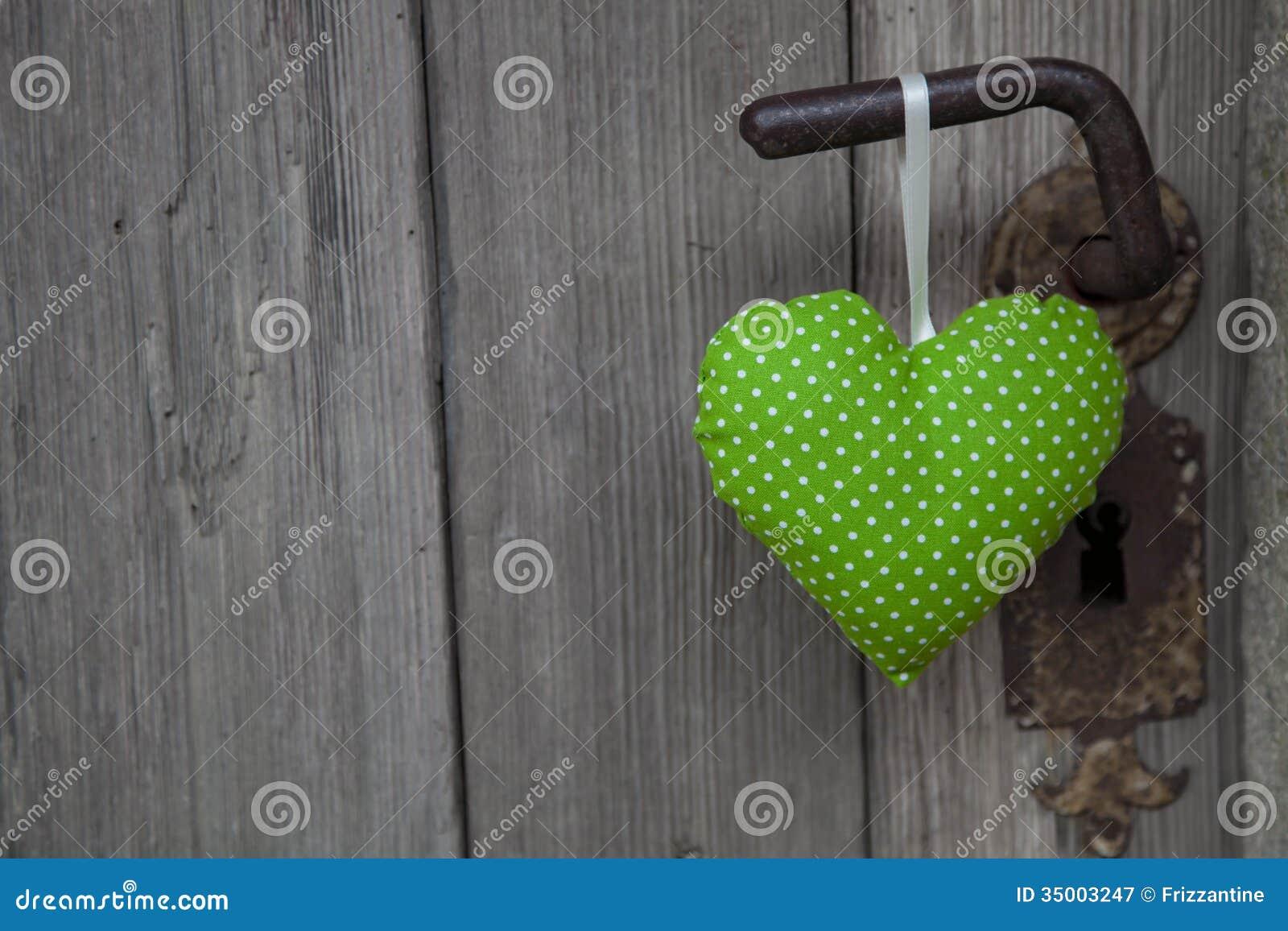 Πράσινη ένωση μορφής καρδιών στη λαβή πορτών - ξύλινο πνεύμα υποβάθρου
