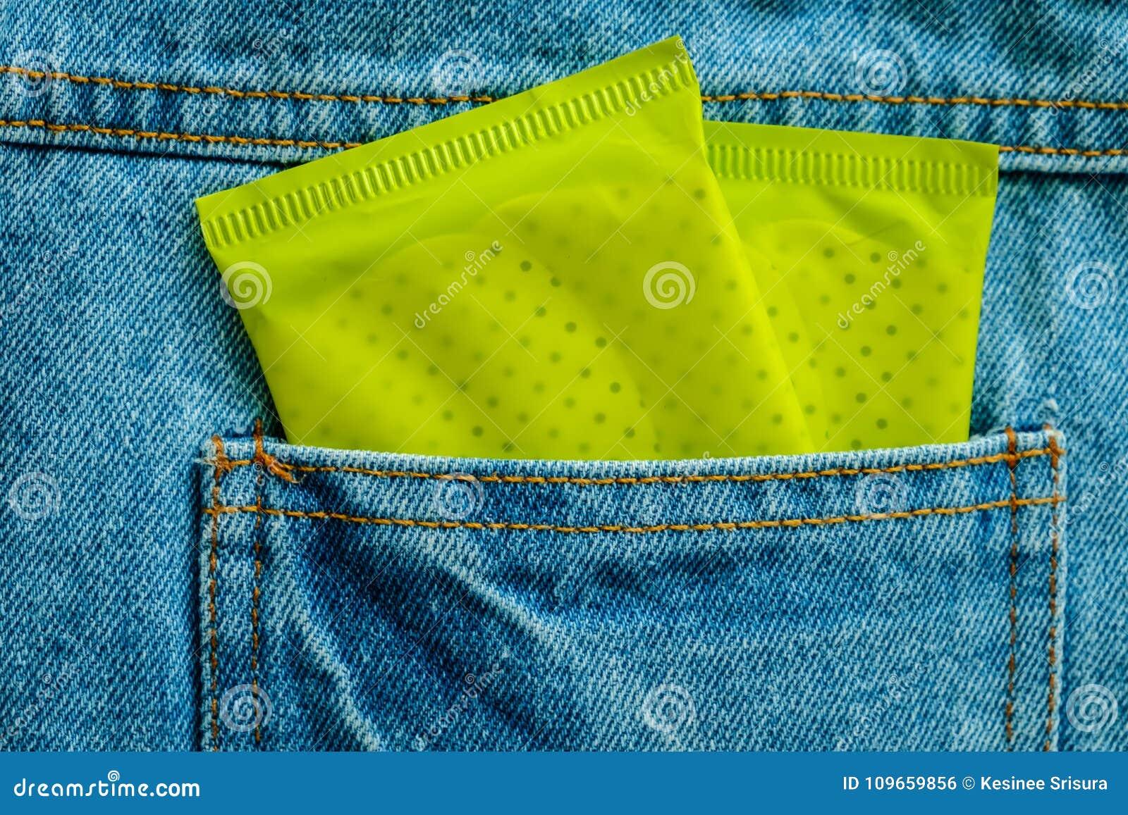 Πράσινη συσκευασία της θηλυκής υγειονομικής πετσέτας στο πίσω μέρος του μπλε τσεπών