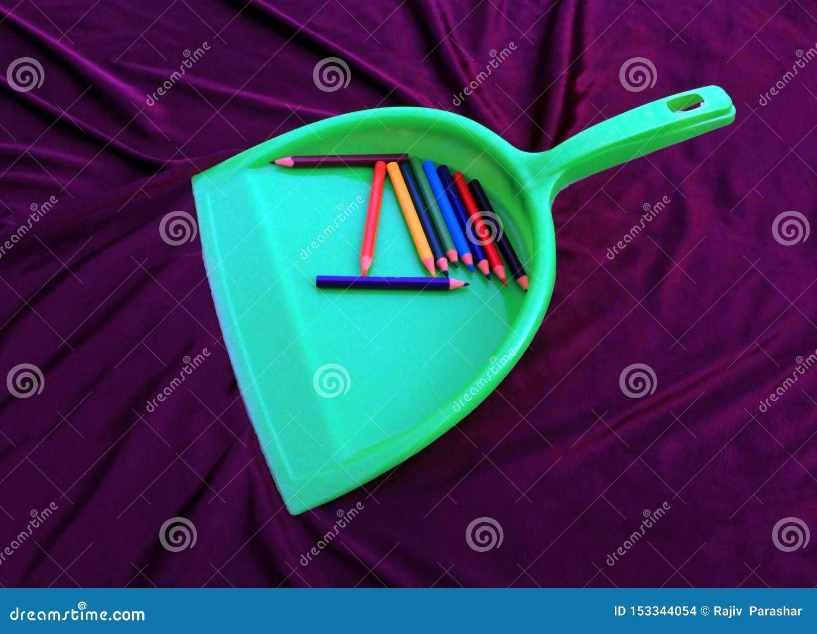 Πράσινος καθαριστής απορριμάτων με το μολύβι που απομονώνεται στο μαύρο υπόβαθρο