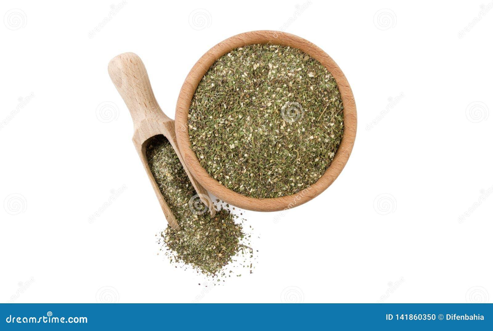 Πράσινο αλμυρό μίγμα ή Chubritsa στο ξύλινο κύπελλο και σέσουλα που απομονώνεται στο άσπρο υπόβαθρο Τοπ όψη Καρυκεύματα και συστα