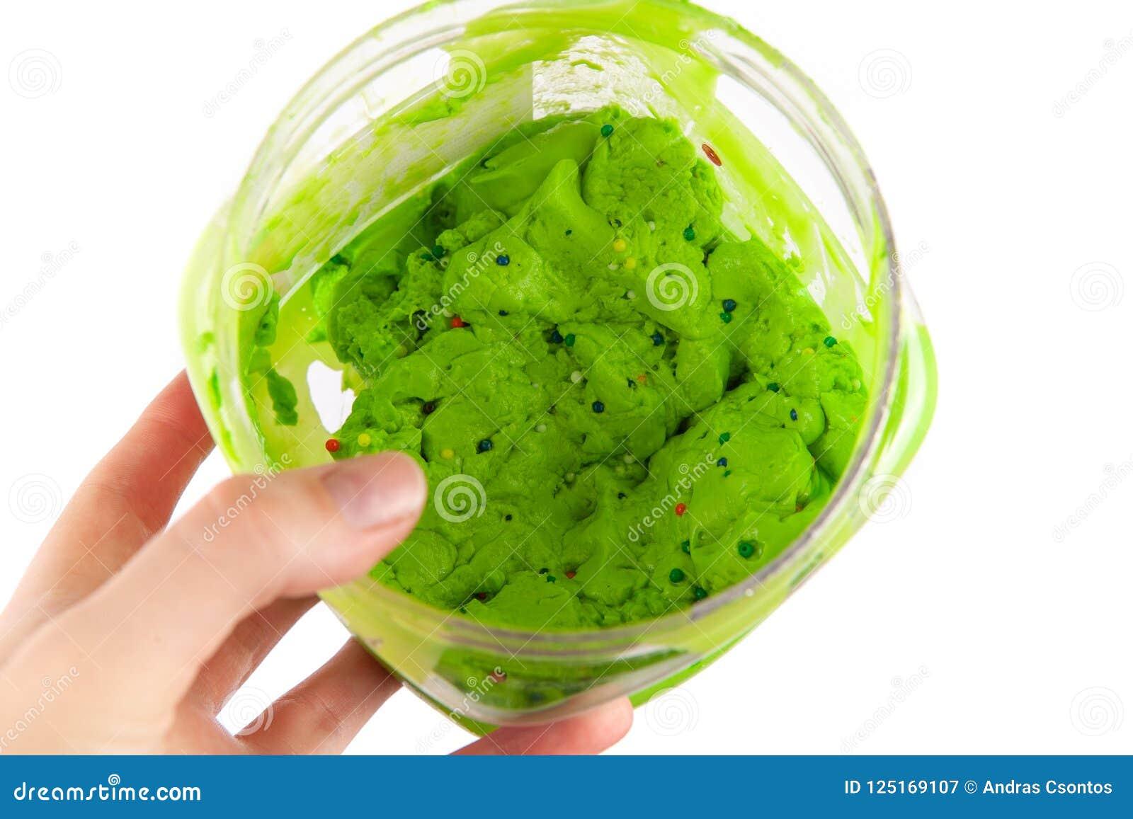 Πράσινο slime νύχτας σε ένα πλαστικό κιβώτιο που απομονώνεται στο άσπρο υπόβαθρο