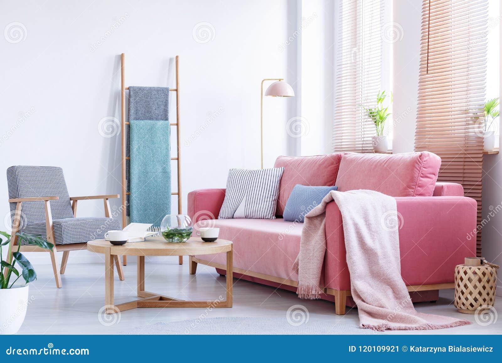 Πραγματική φωτογραφία ένας ρόδινος καναπές με τα μαξιλάρια και κάλυμμα που στέκεται στο α