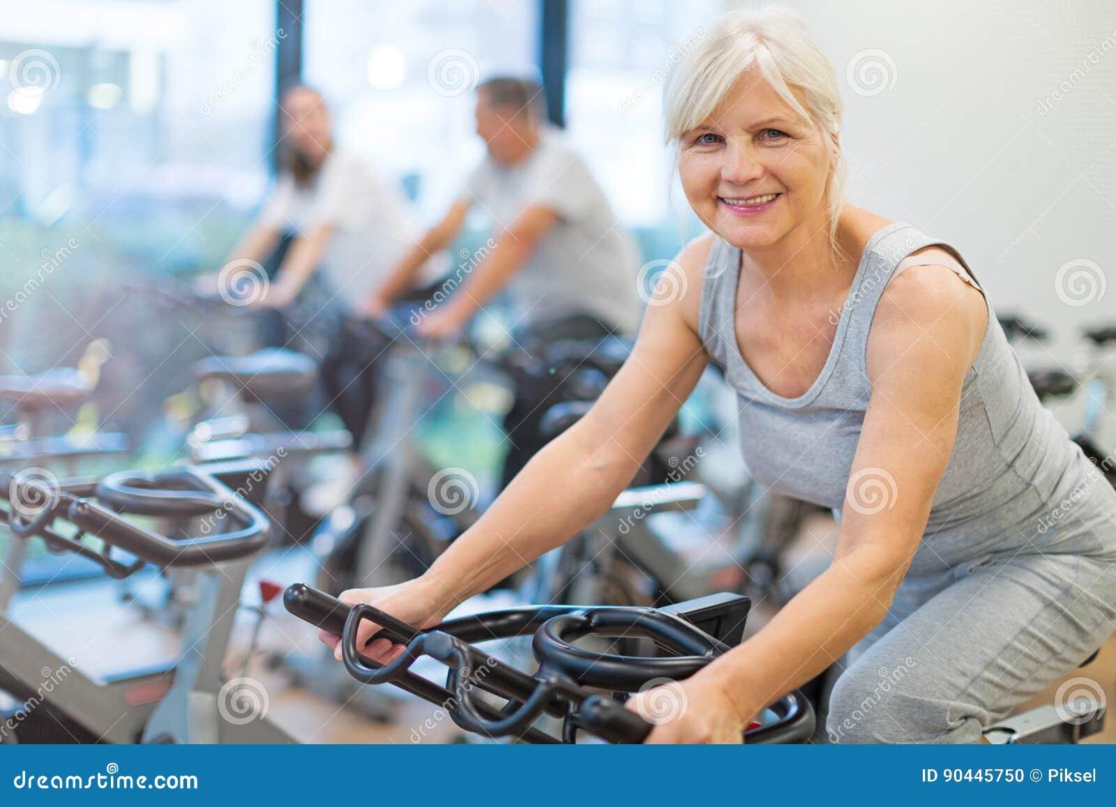 Πρεσβύτεροι στα ποδήλατα άσκησης στην περιστροφή της κατηγορίας στη γυμναστική