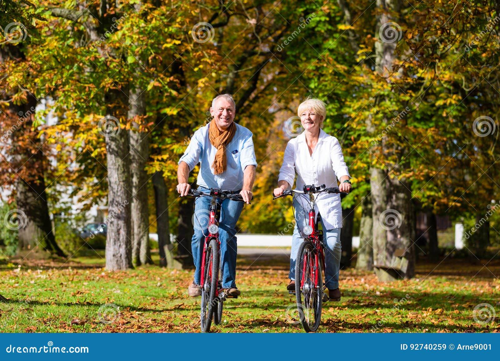 Πρεσβύτεροι στα ποδήλατα που έχουν το γύρο στο πάρκο