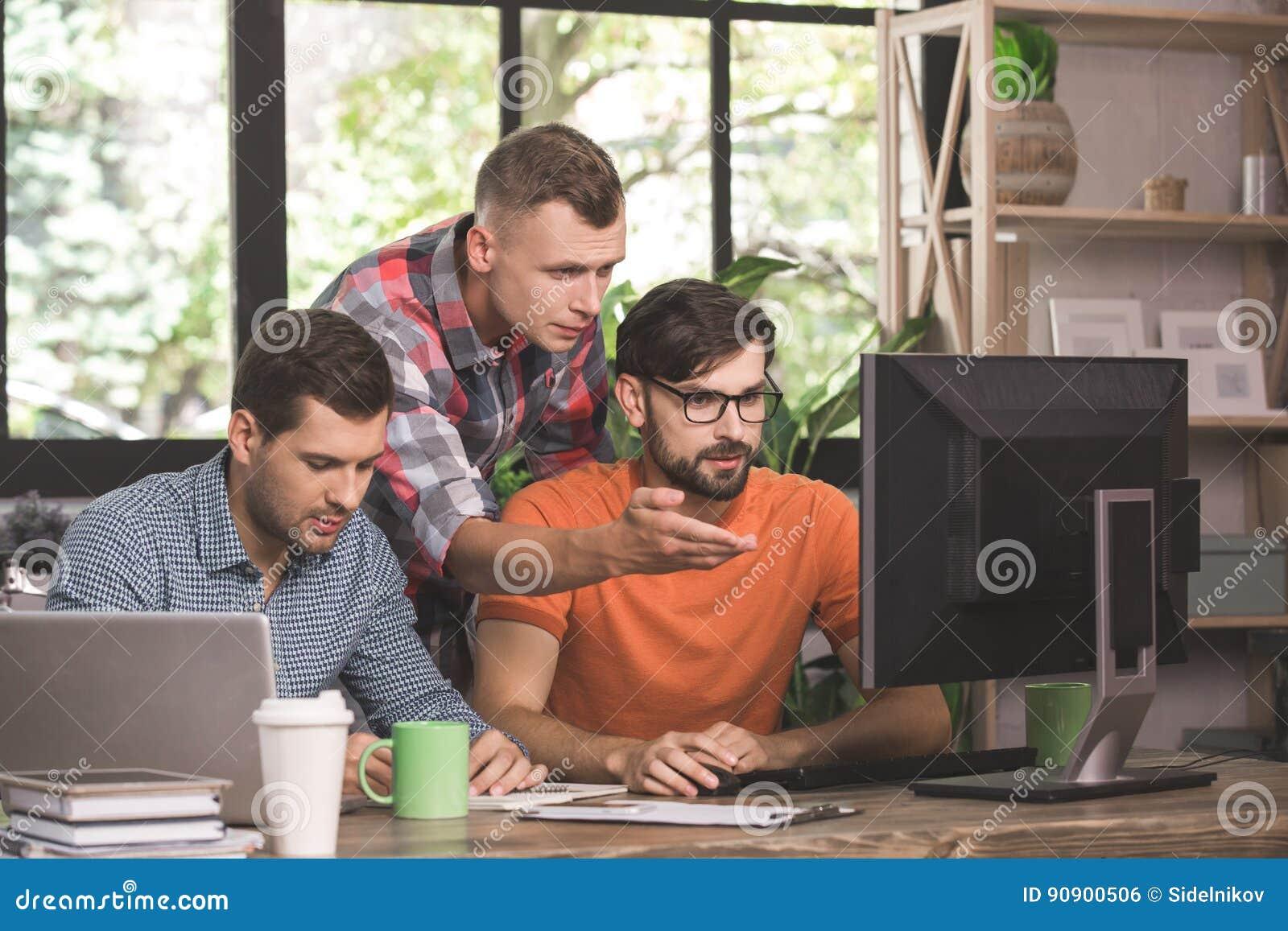 Προγραμματιστές νεαρών άνδρων που εργάζονται μαζί στο γραφείο