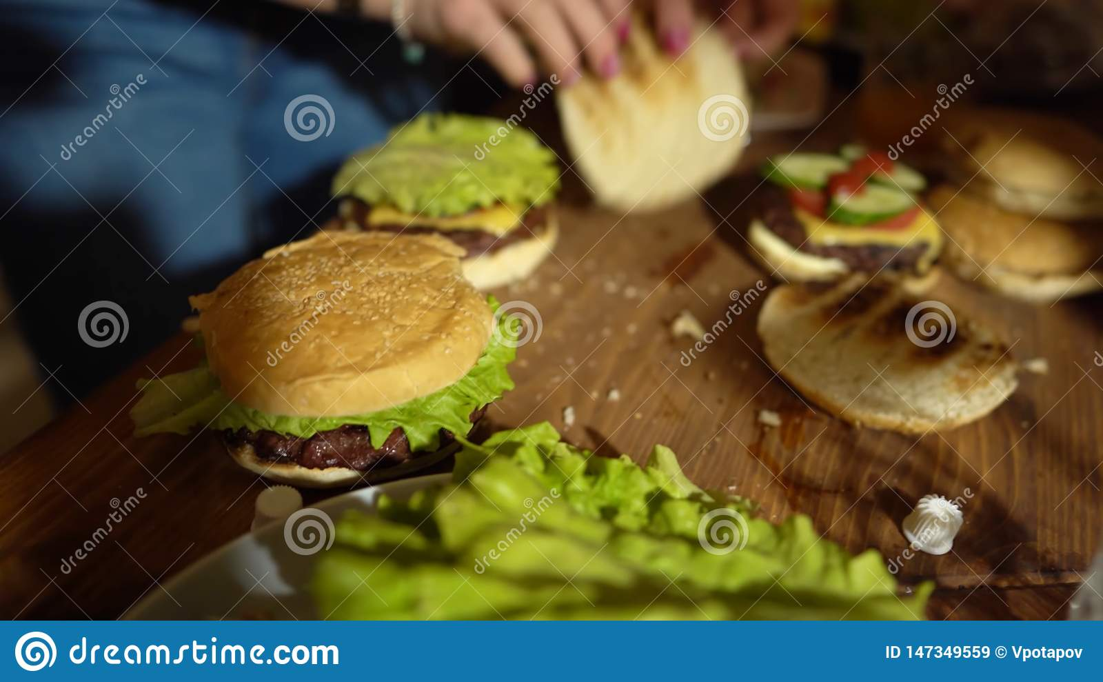 Προετοιμάζοντας τα χάμπουργκερ, που κατασκευάζουν το χάμπουργκερ, τα συστατικά για τα burgers μαγειρέματος, τα λαχανικά, το τυρί