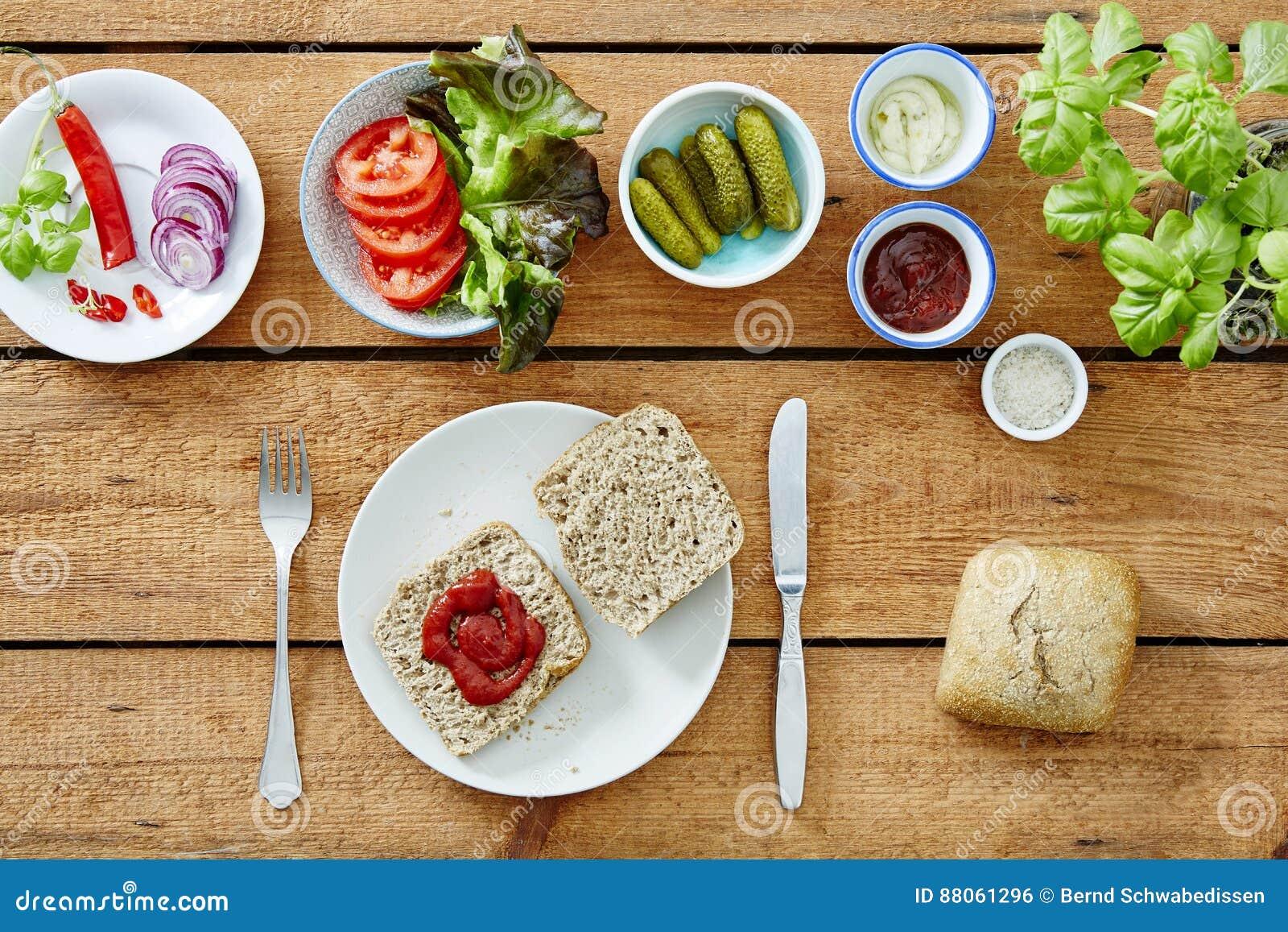 Προετοιμασία ενός vegan σάντουιτς που βάζει tomatoe τη σάλτσα στο bredrole