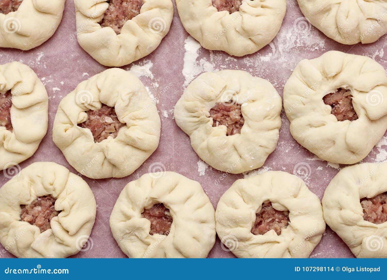 Προετοιμασία των belyashes Παραδοσιακό ρωσικό belyashi πιτών κρέατος belyashes σε έναν πίνακα Ρωσική, από το $λ* ψασχκηρ και Tata