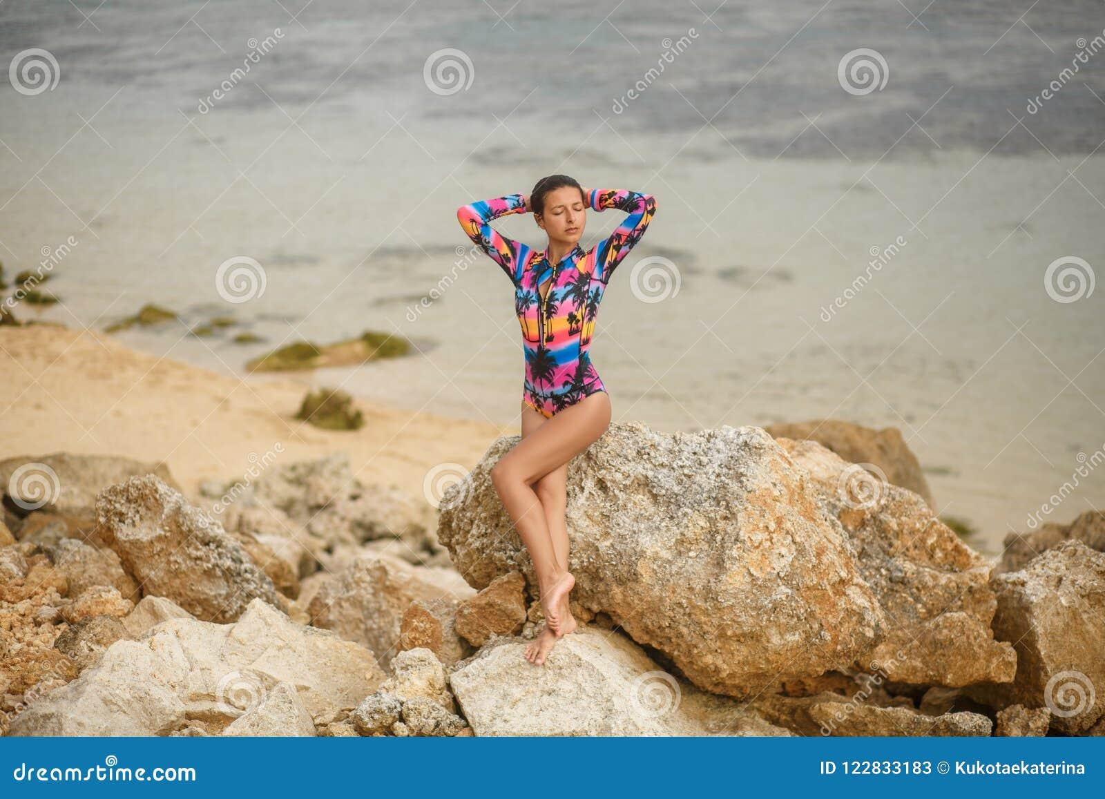 Προκλητικό κορίτσι που θέτει τη συνεδρίαση στους βράχους στην παραλία