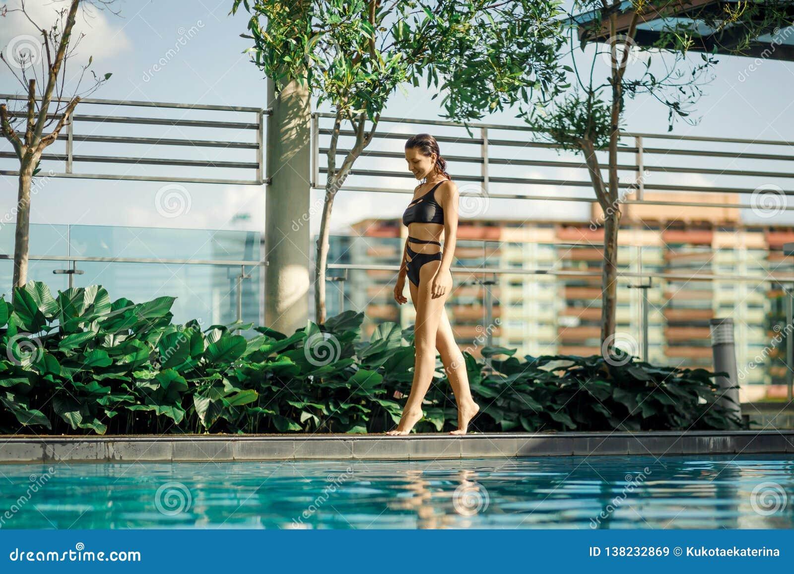 Προκλητικό λεπτό καυκάσιο brunette που περπατά μεταξύ των πράσινων Μπους και των δέντρων στην άκρη της πισίνας στη στέγη με τη ει
