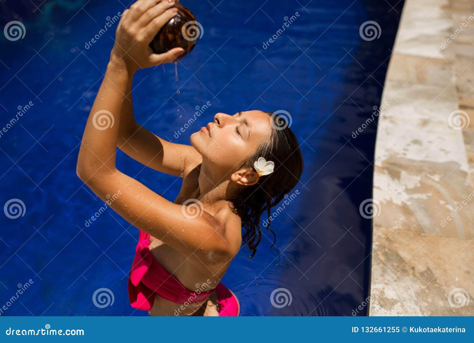 Προκλητικό λεπτό νέο θηλυκό brunette που ποτίζεται με το φρέσκο γάλα καρύδων στη λίμνη με το μπλε νερό κρυστάλλου Βασιλικό τροπικ