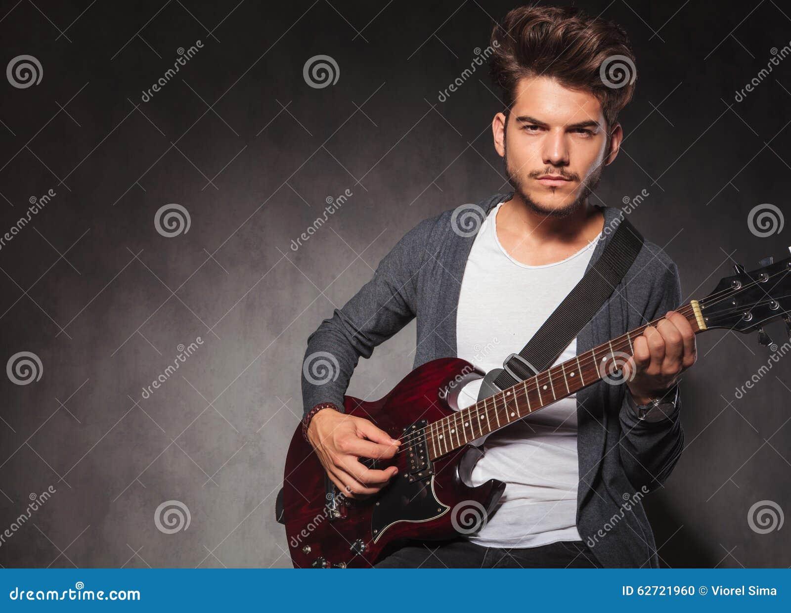 Προκλητική κιθάρα παιχνιδιού ατόμων που εξετάζει τη κάμερα