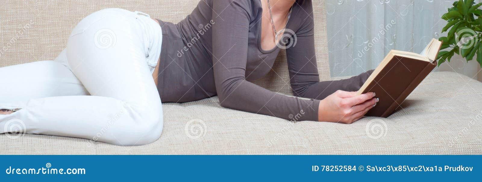 Προκλητική νέα γυναίκα που βρίσκεται στο κρεβάτι και που διαβάζει το βιβλίο στο σπίτι