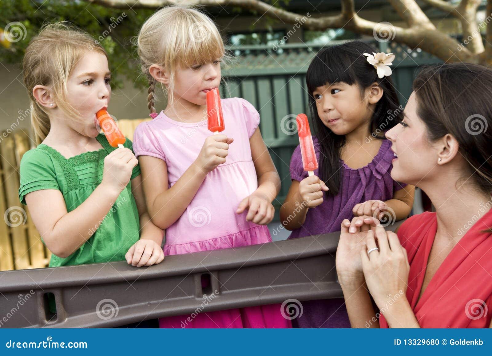 Προσχολικά παιδιά στην παιδική χαρά με το δάσκαλο
