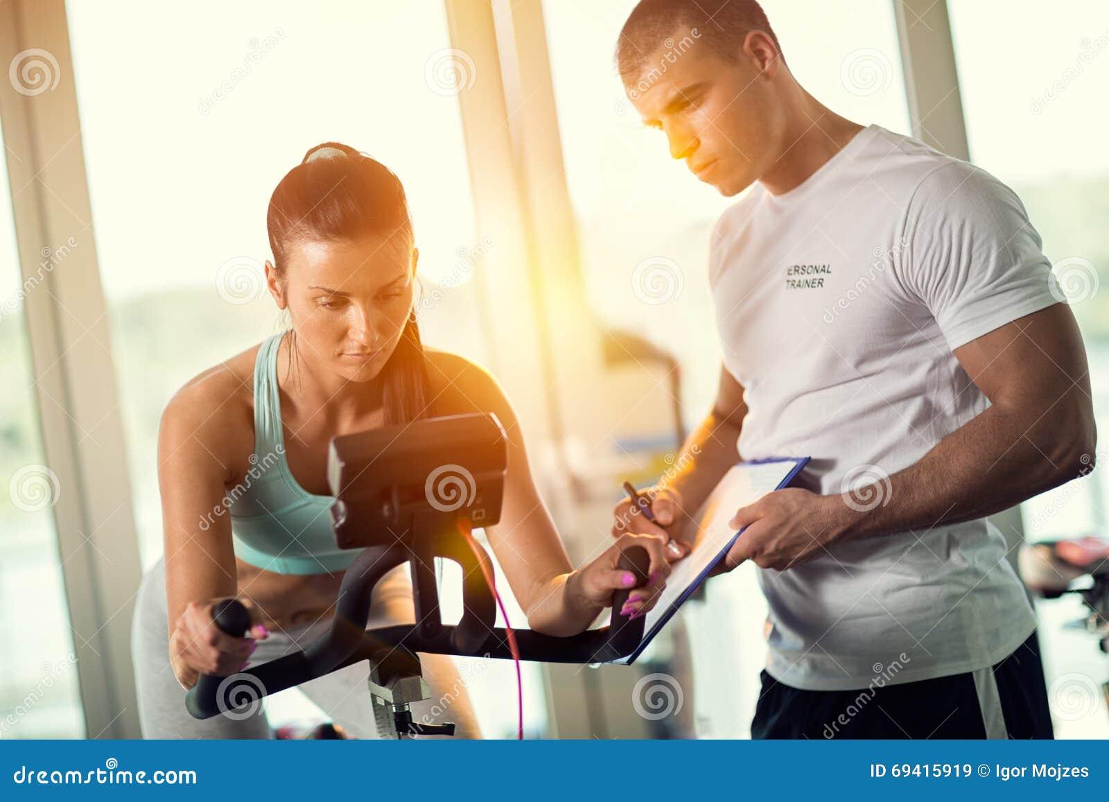 Προσωπικοί εκπαιδευτές στη γυμναστική που δίνει την οδηγία και τη βοήθεια στο attr