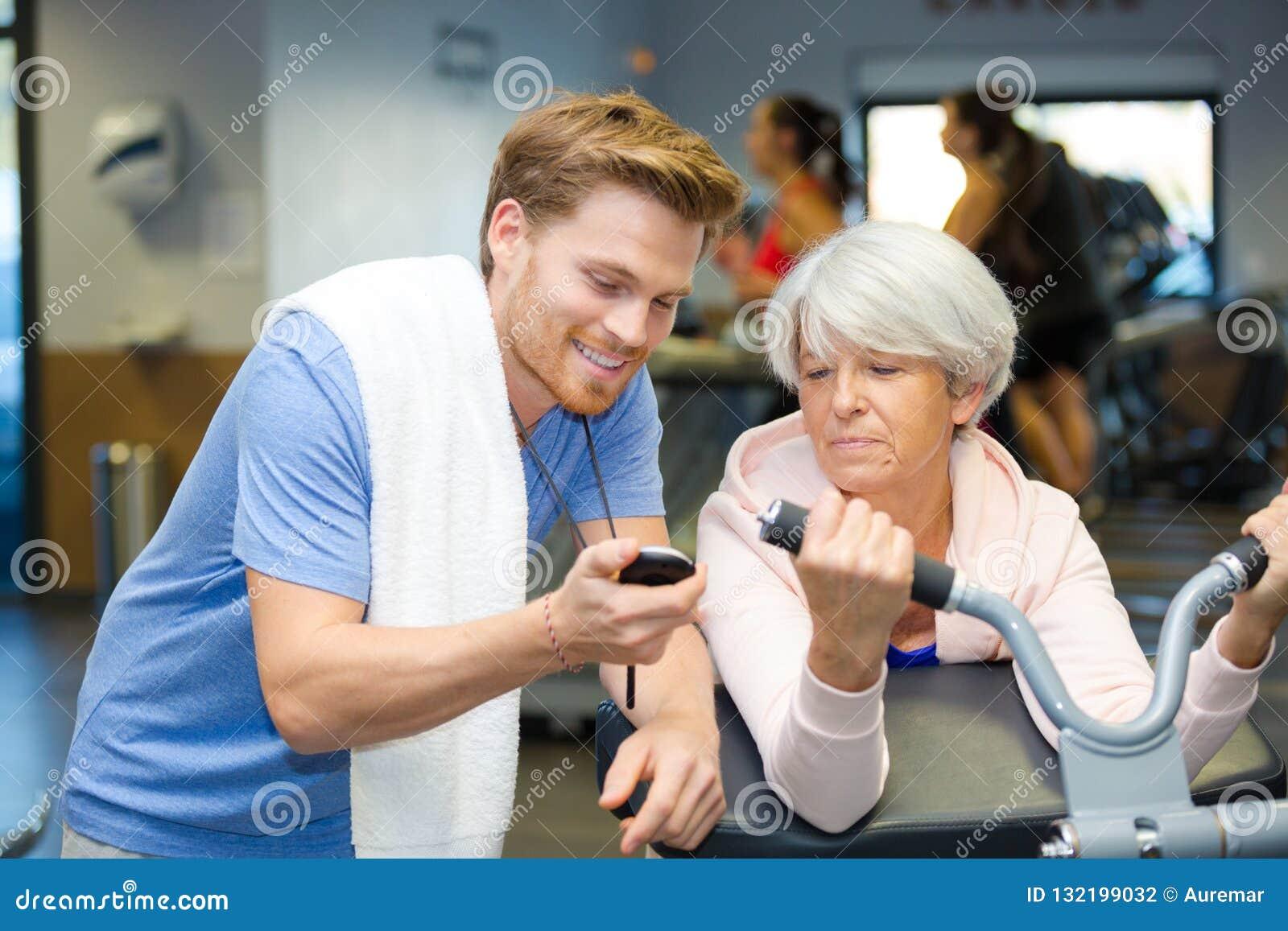 Προσωπικός εκπαιδευτής που παρουσιάζει χρόνο χρονομέτρων με διακόπτη στον ανώτερο πελάτη