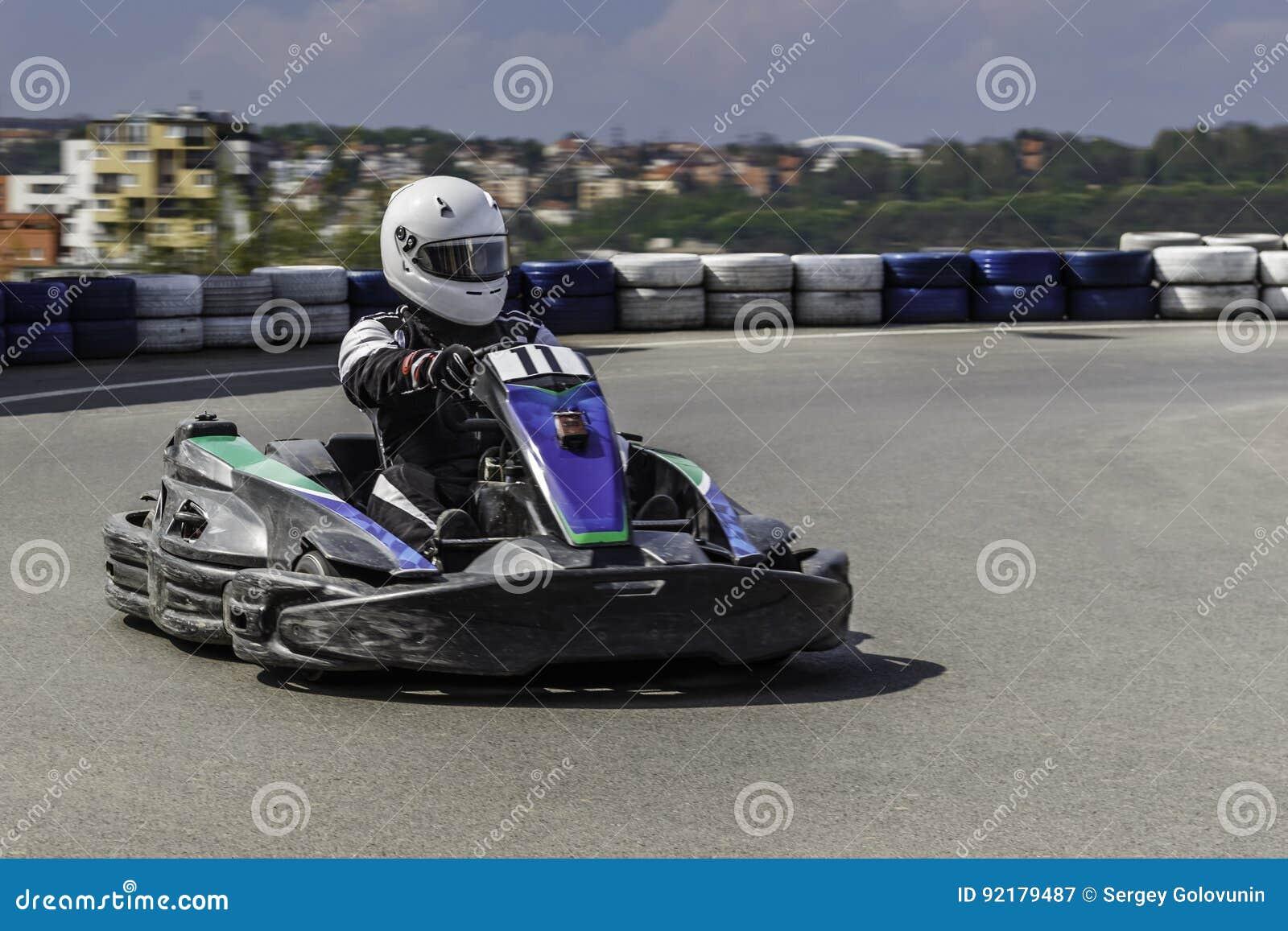Πρωτάθλημα Karting Ο οδηγός στα karts που φορούν το κράνος, συναγωνιμένος το κοστούμι συμμετέχει στη φυλή kart Το Karting παρουσι
