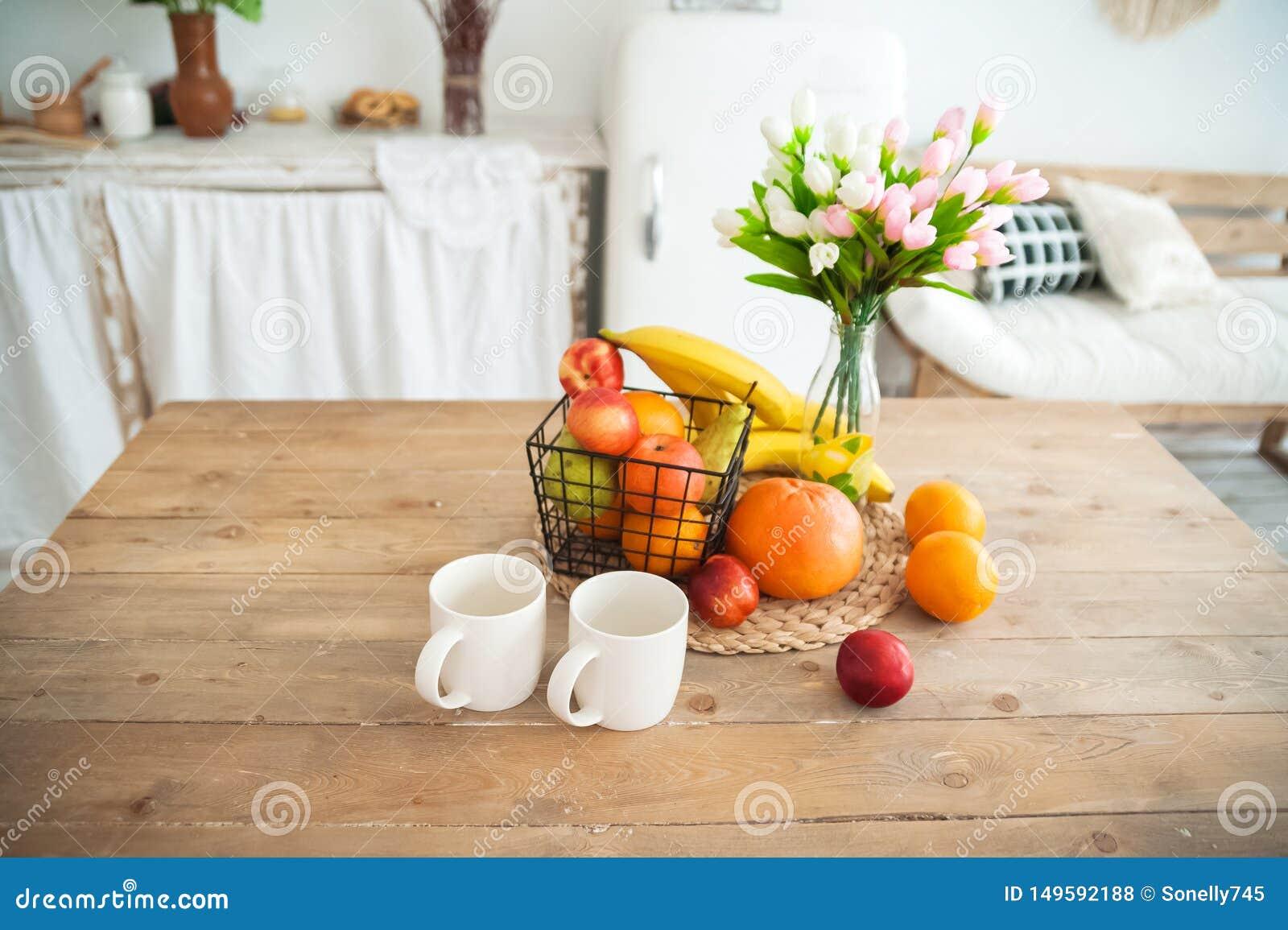Πρόγευμα έννοιας που γίνεται από τα φρούτα και τον καφέ ή το τσάι Πορτοκάλια, μπανάνες, φλυτζάνια, ροδάκινα σε έναν της υφής μεγά