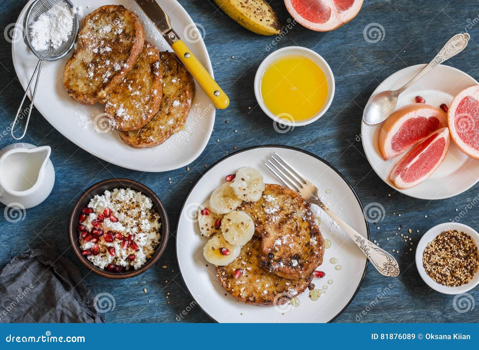Πρόγευμα - γαλλική φρυγανιά καραμέλας με την μπανάνα, τυρί εξοχικών σπιτιών με το granola και ρόδι, φρέσκο γκρέιπφρουτ σε ένα μπλ