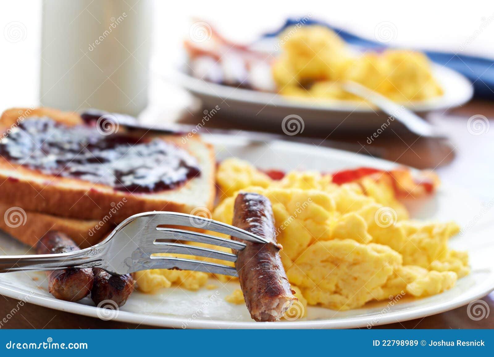 Πρόγευμα με τις συνδέσεις λουκάνικων και τα ανακατωμένα αυγά.