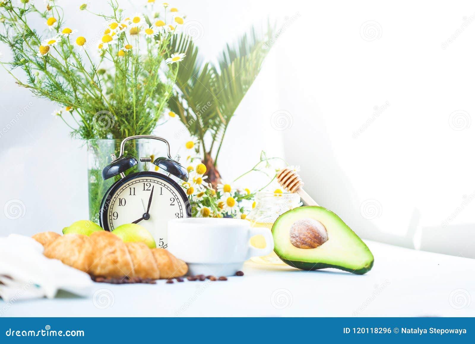 Πρόγευμα πρωινού, καφές σε ένα άσπρο αβοκάντο Croissant φλυτζανιών που ξυπνά με ένα φρέσκο αντίγραφο SP προγευμάτων ξυπνητηριών ε