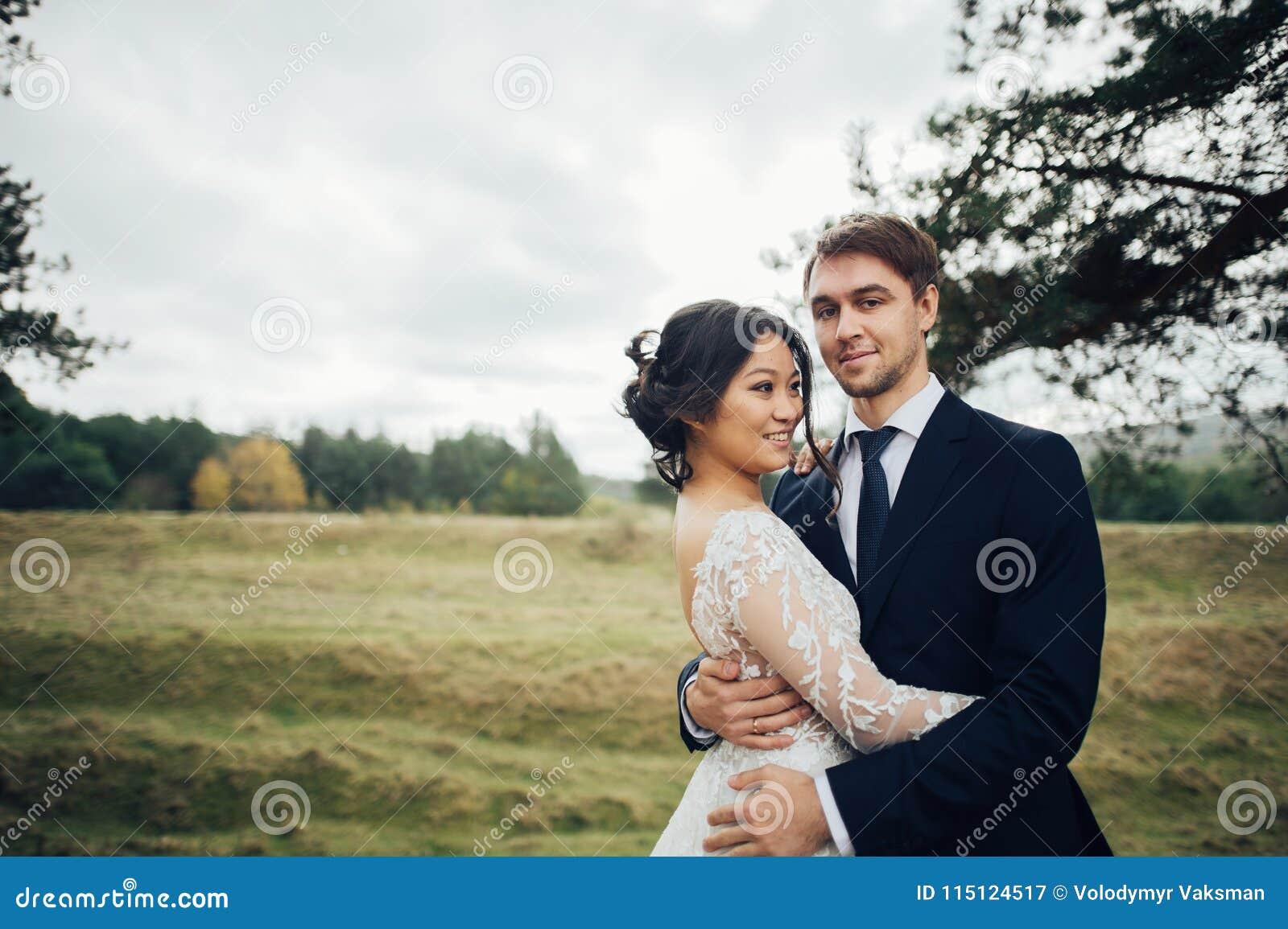 Πρόσφατα το ζεύγος που φιλά tenderly μεταξύ των κομψών δέντρων