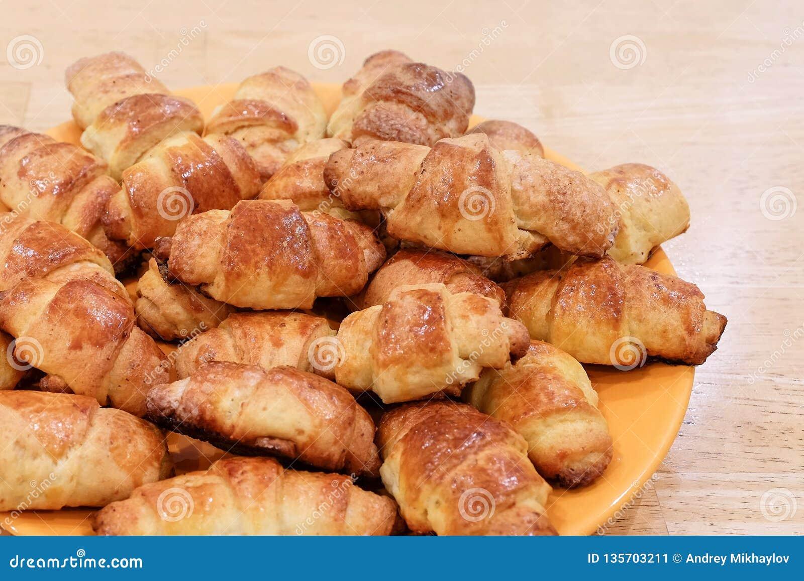 Πρόσφατα ψημένος croissants στον ξύλινο τέμνοντα πίνακα, τοπ άποψη
