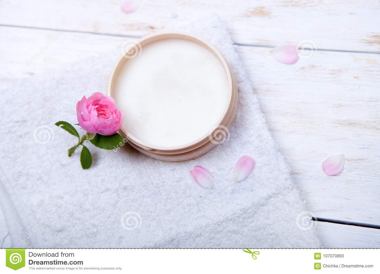 Πρόσωπο-κρέμα και λουλούδι σε ένα άσπρο ξύλινο υπόβαθρο φυσικός οργανικός καλλυντικός του προσώπου