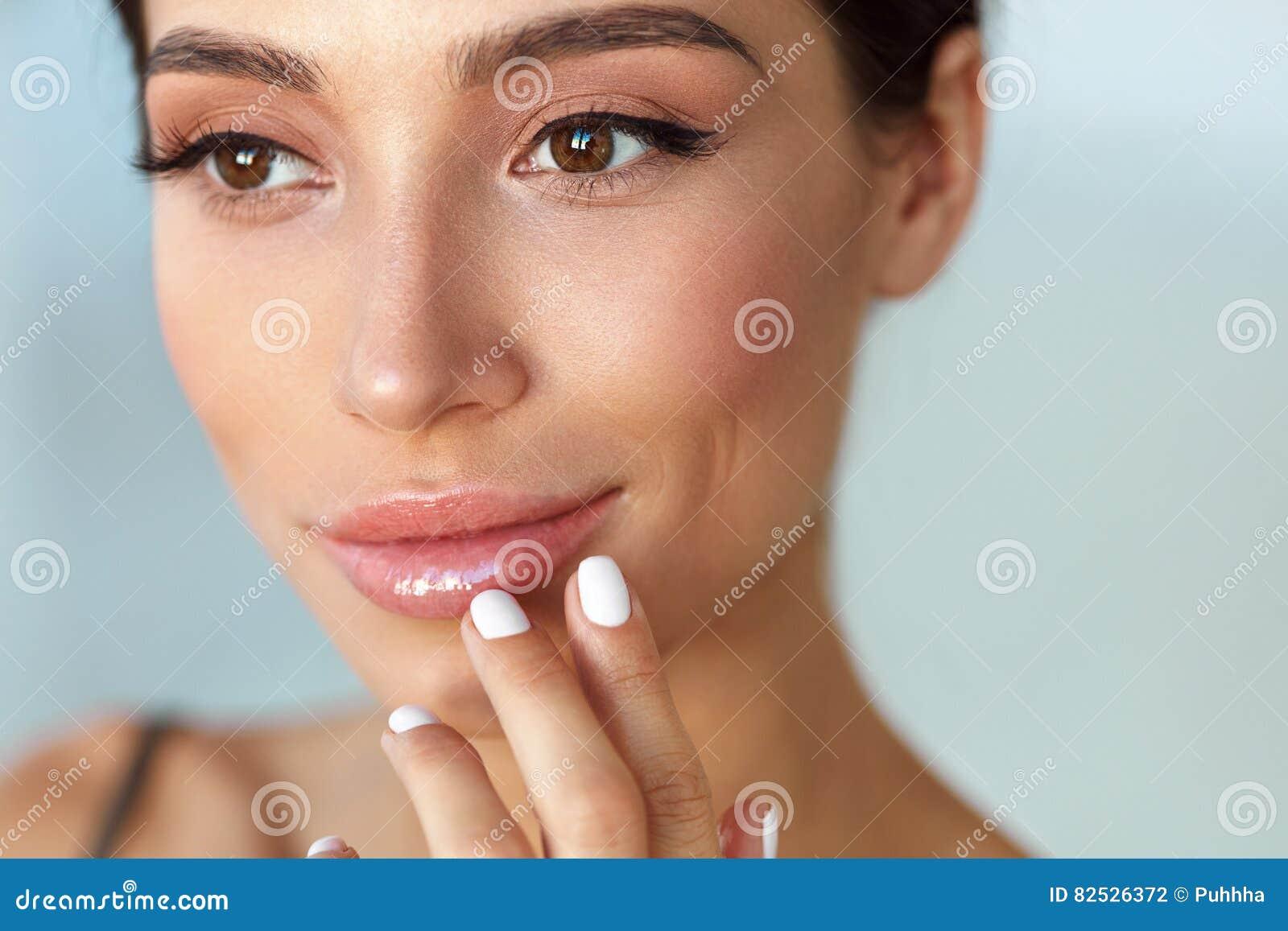 Πρόσωπο ομορφιάς Όμορφη γυναίκα σχετικά με τα χείλια με το χειλικό βάλσαμο επάνω
