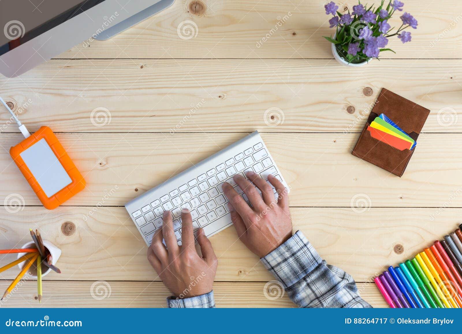 Πρόσωπο που εργάζεται στην ελαφριά ξύλινη άποψη υπολογιστών γραφείου