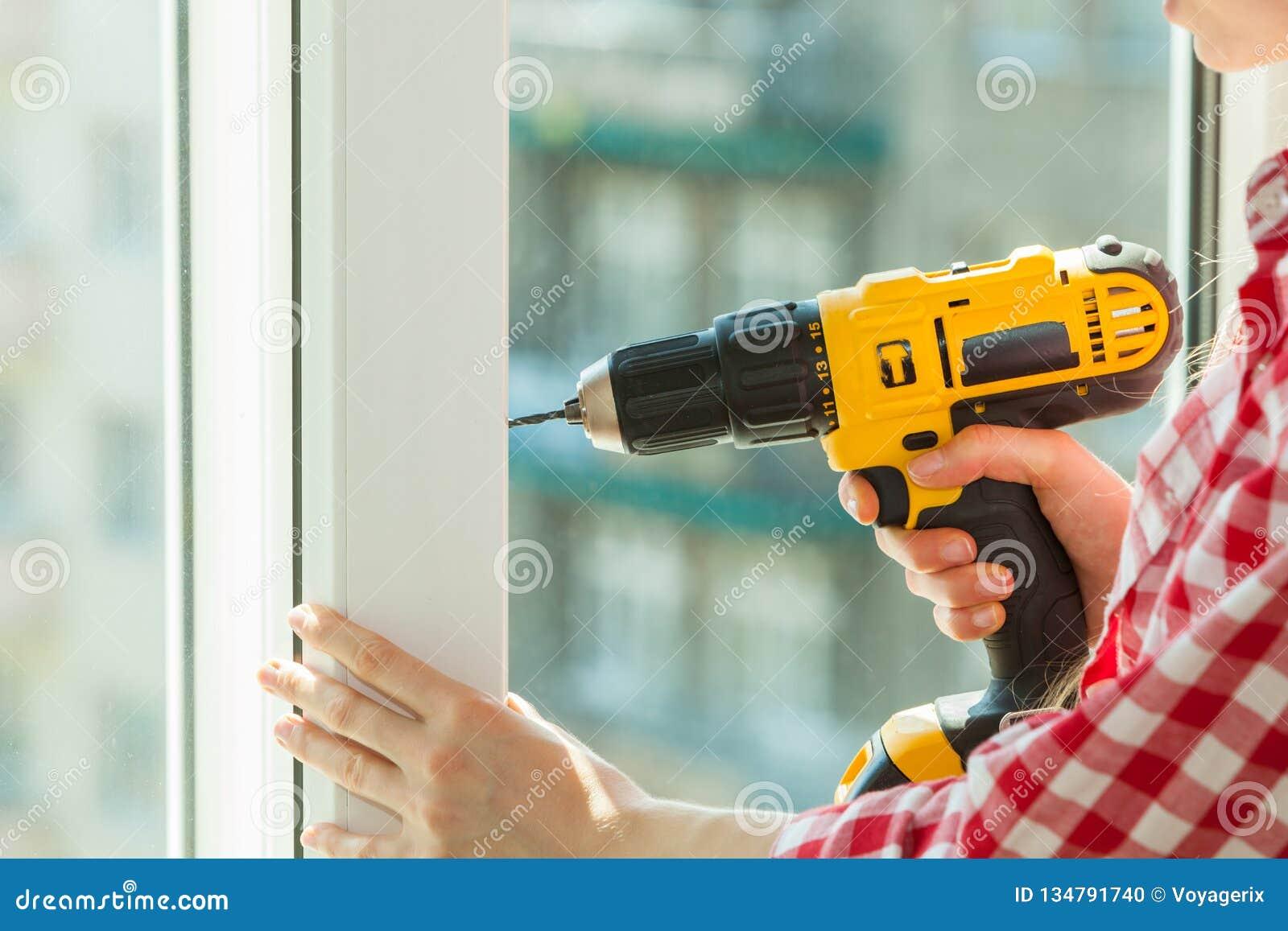 Πρόσωπο που χρησιμοποιεί το τρυπάνι στο παράθυρο