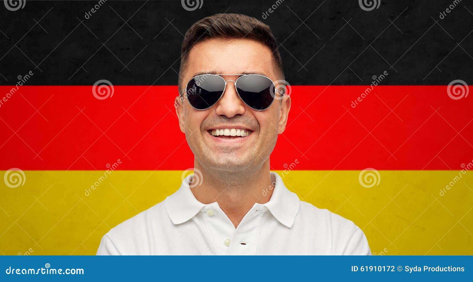 Πρόσωπο του χαμογελώντας ατόμου στα γυαλιά ηλίου πέρα από τη γερμανική σημαία
