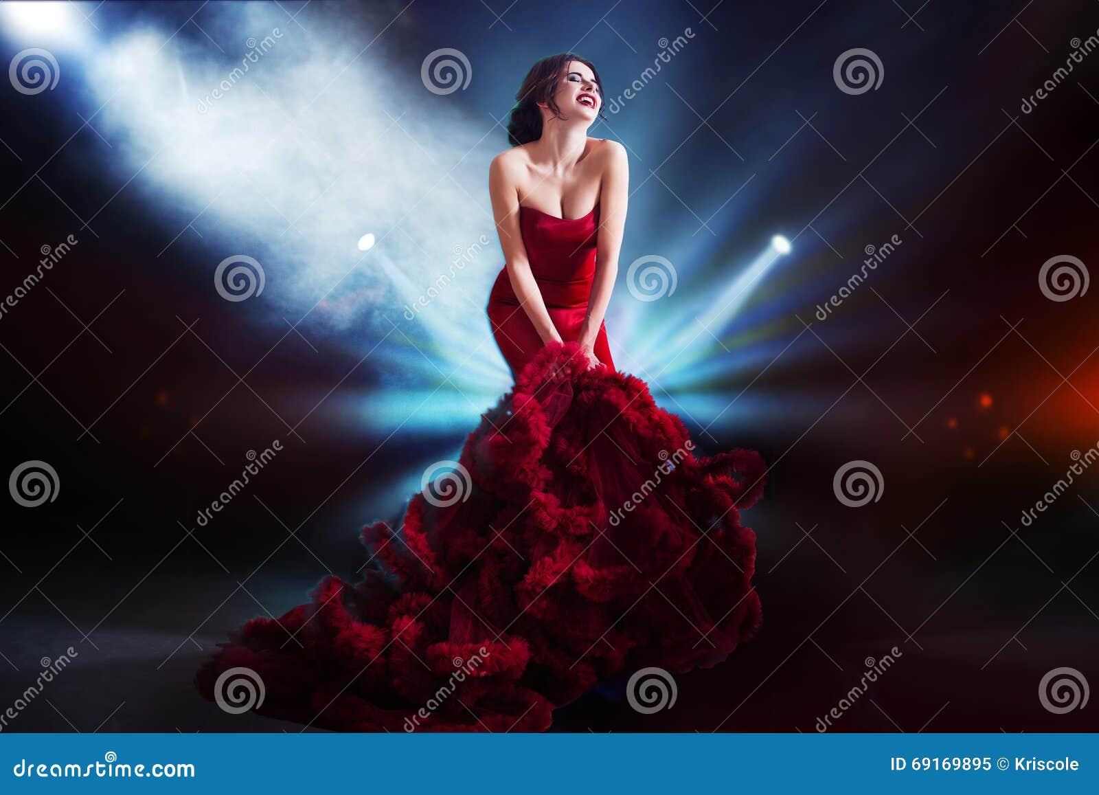 Πρότυπη γυναίκα Brunette ομορφιάς στο κόκκινο φόρεμα βραδιού Όμορφη πολυτέλεια μόδας makeup και hairstyle Σκοτεινό υπόβαθρο, φως