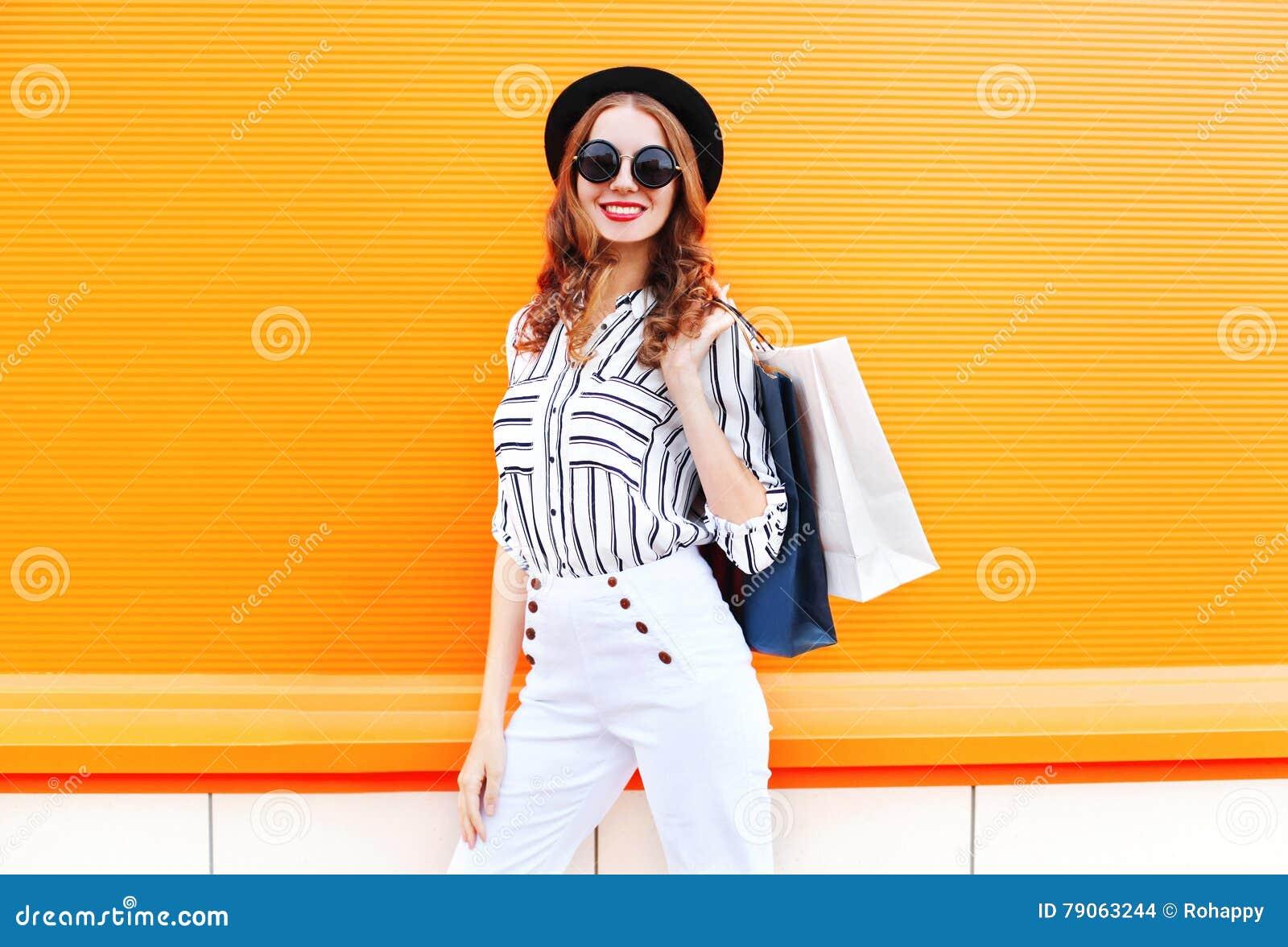 Πρότυπο γυναικών χαμόγελου μόδας αρκετά νέο με τις τσάντες αγορών που φορούν τα άσπρα εσώρουχα μαύρων καπέλων πέρα από το ζωηρόχρ