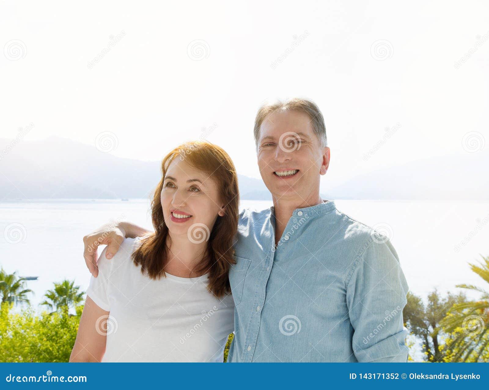Πρότυπο θερινών άσπρο μπλουζών Ευτυχές μέσο ηλικίας οικογενειακό ζεύγος στις διακοπές Παραλία και έννοια διακοπών Διάστημα και χλ