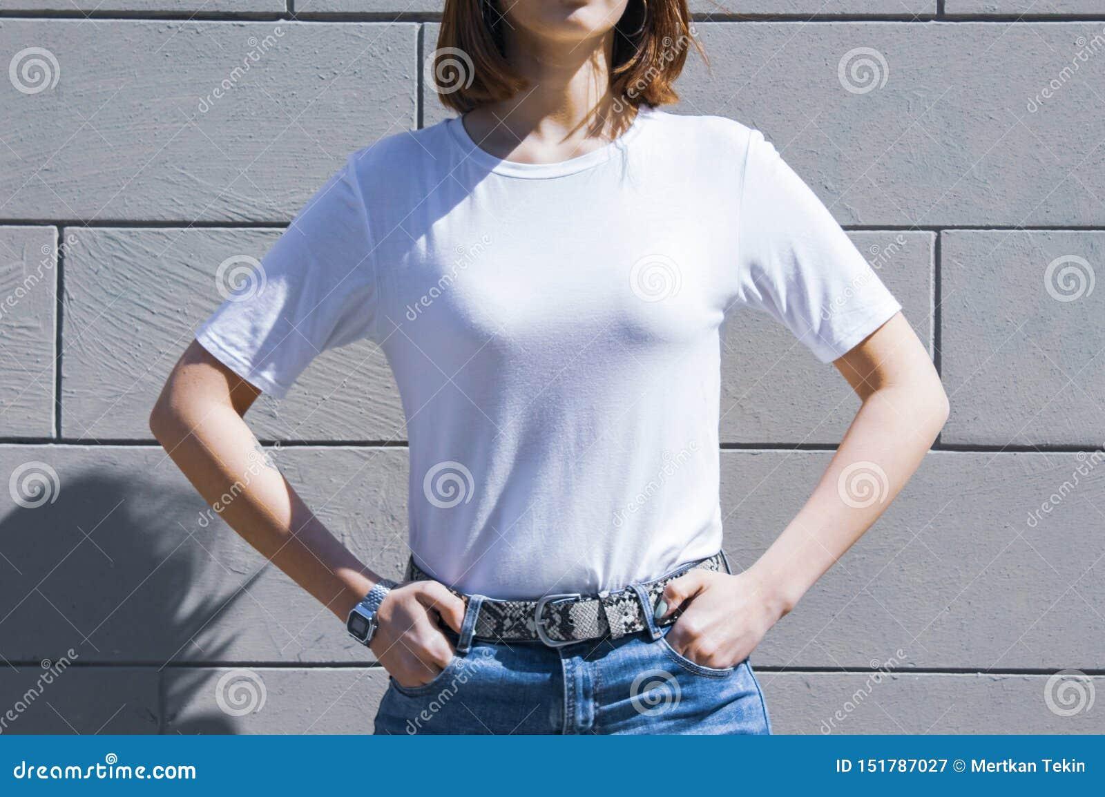 Πρότυπο και κενή άσπρη τοποθέτηση μπλουζών και τζιν προτύπων ενάντια στον γκρίζο τοίχο οδών, για το κατάστημα τυπωμένων υλών