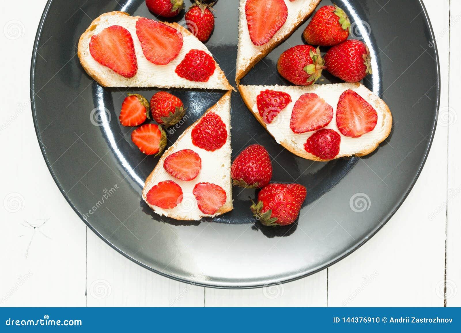 Πρόχειρα φαγητά των φρέσκων σάντουιτς με τις φράουλες σε έναν άσπρο πίνακα Υγιές πρόγευμα, τοπ άποψη