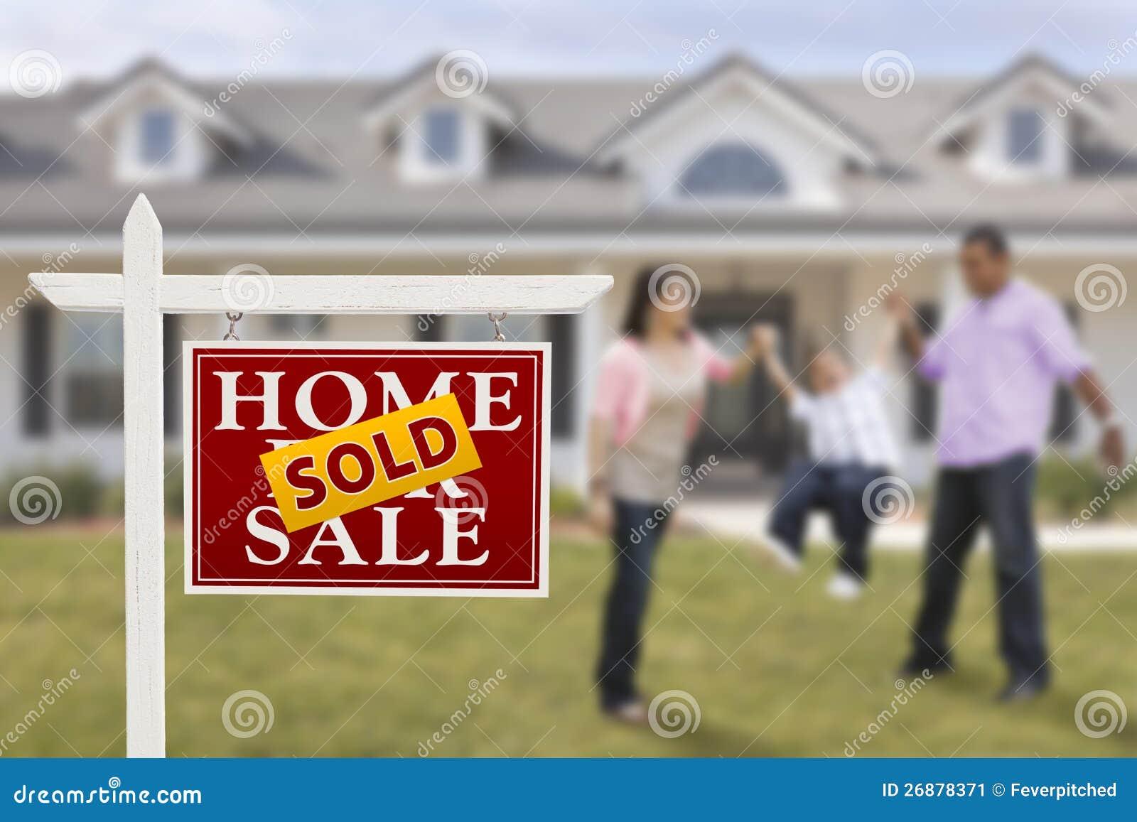 Πωλημένο σημάδι ακίνητων περιουσιών και ισπανική οικογένεια στο σπίτι