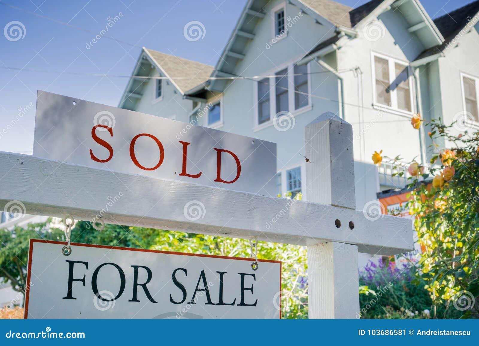 Πωλημένο σημάδι μπροστά από ένα σπίτι σε μια κατοικημένη γειτονιά