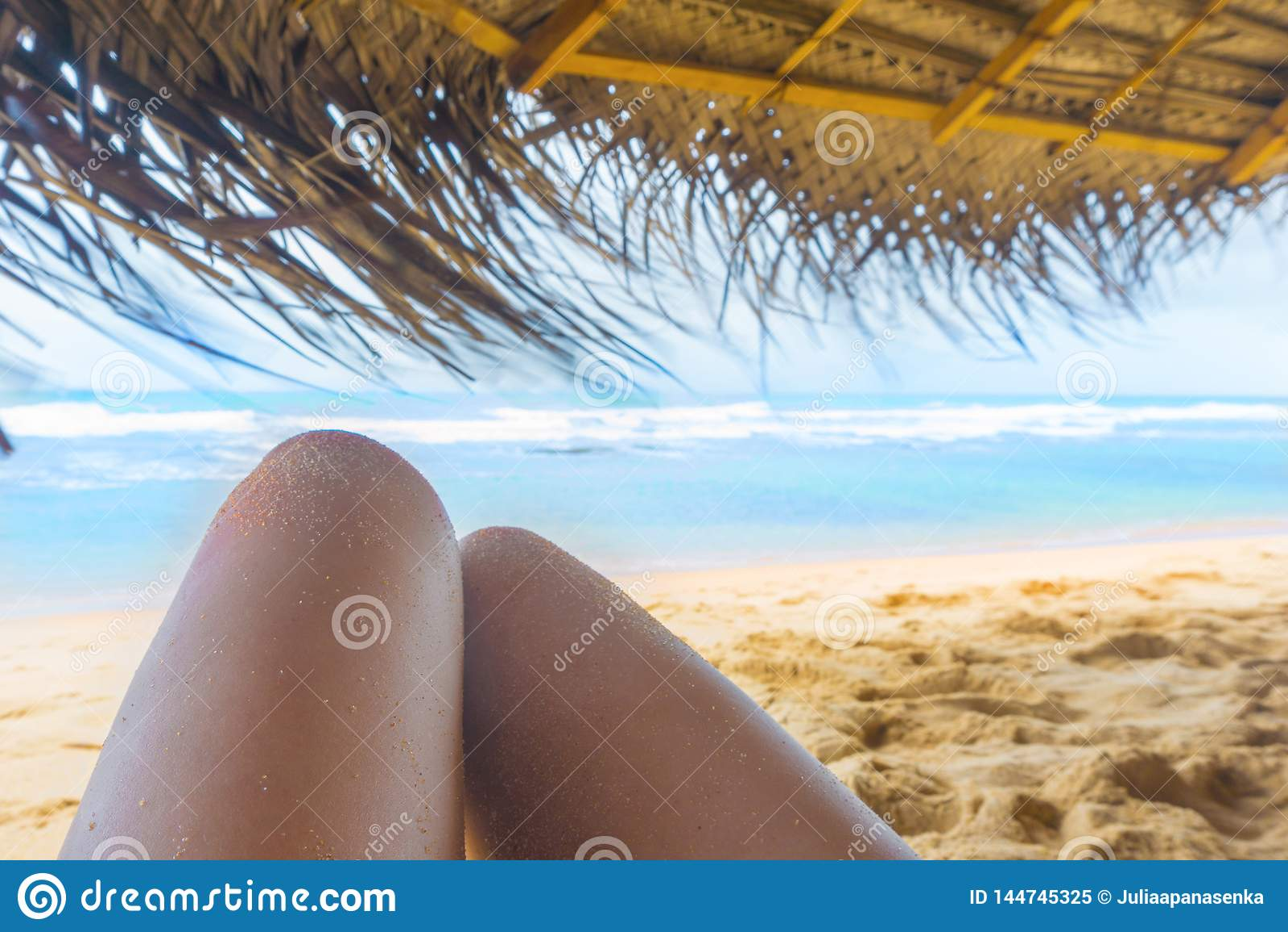 Πόδια γυναίκας κάτω από sunshade στην ηλιόλουστη τροπική παραλία