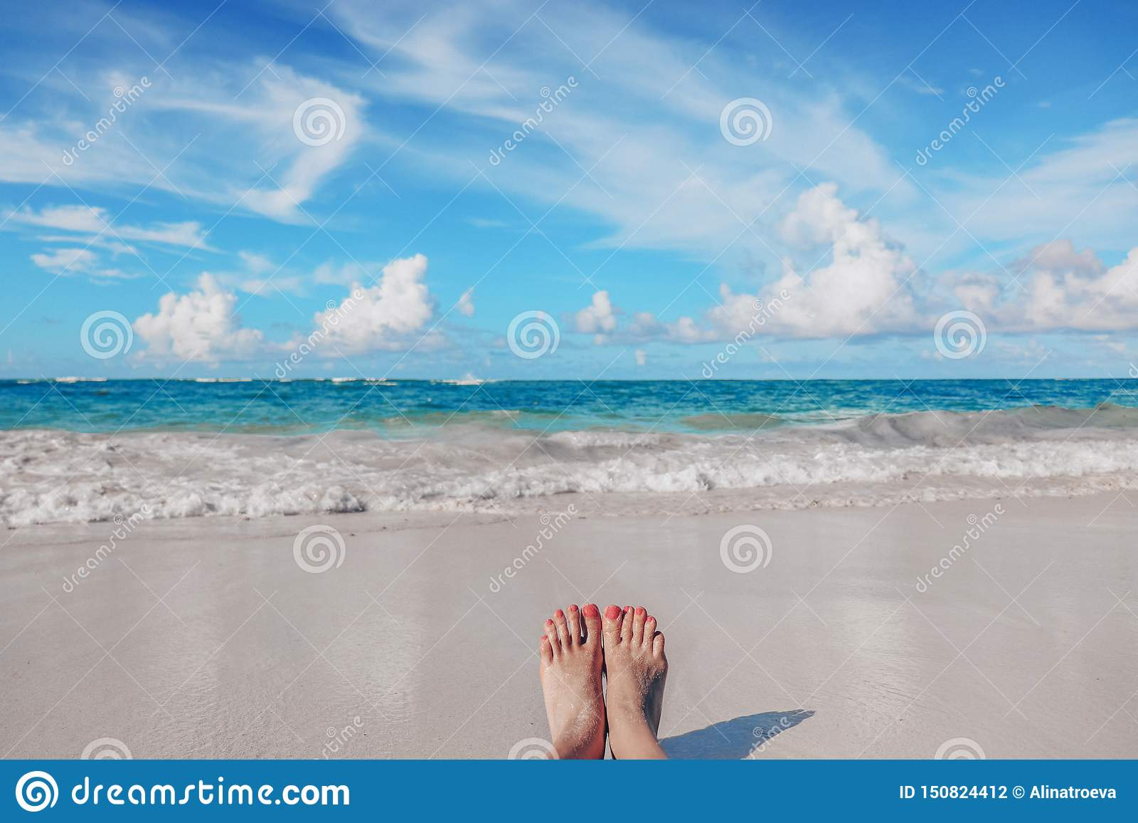 Πόδια γυναίκας στην τροπική καραϊβική παραλία Ωκεανός και μπλε ουρανός
