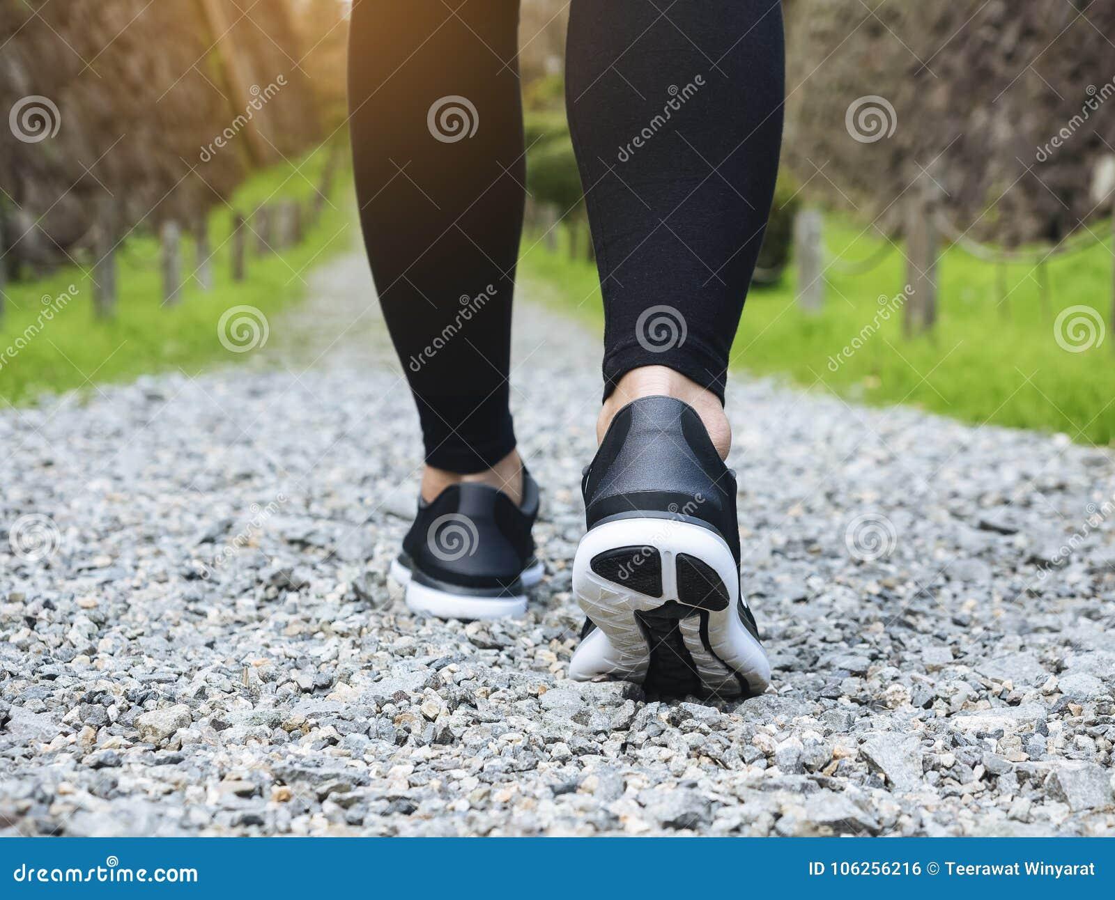 Πόδια γυναικών περπατήματος ιχνών με το πάρκο Trailt αθλητικών παπουτσιών υπαίθριο