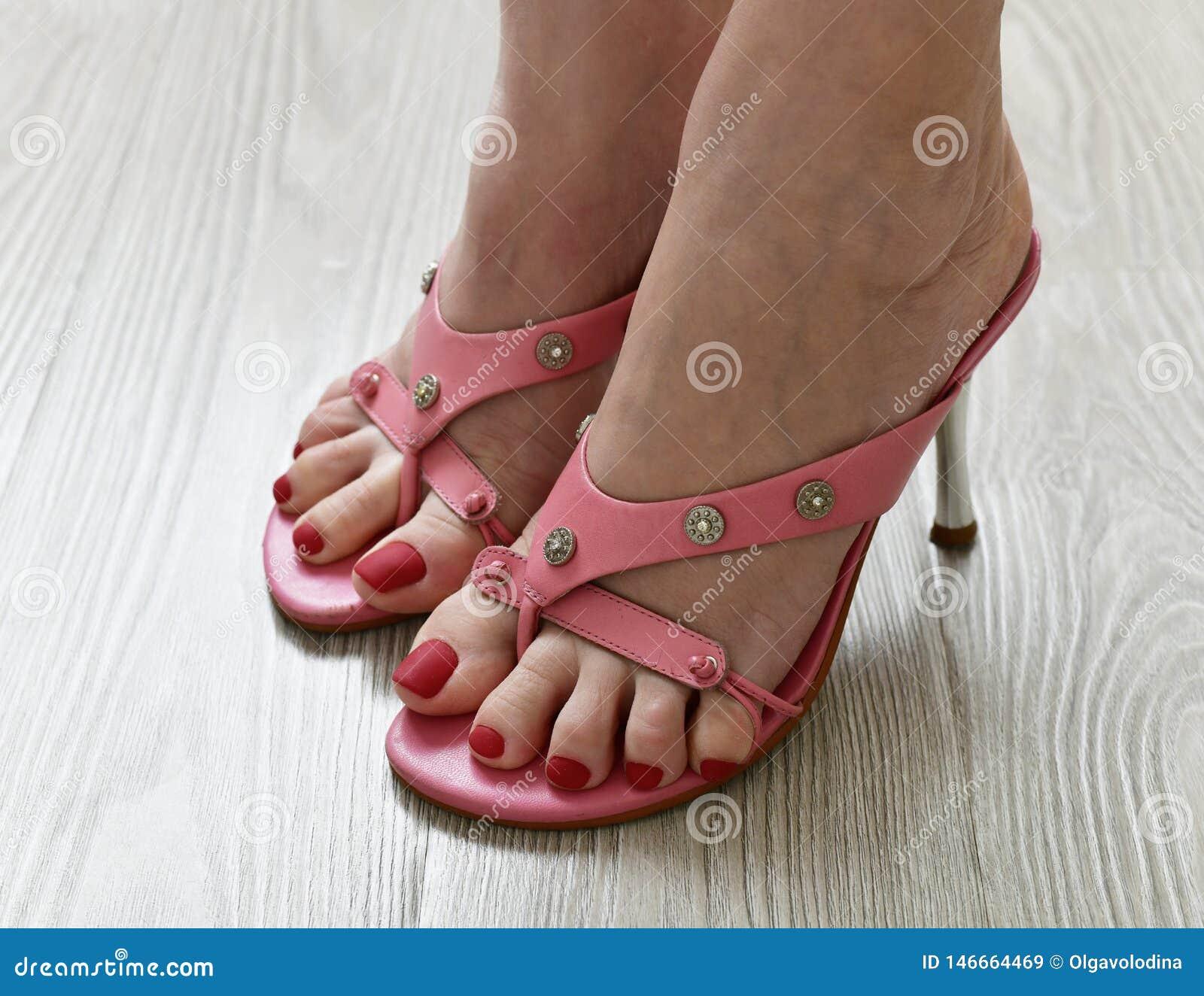 Πόδια γυναικών στα θερινά βαλμένα τακούνια ροζ σανδάλια