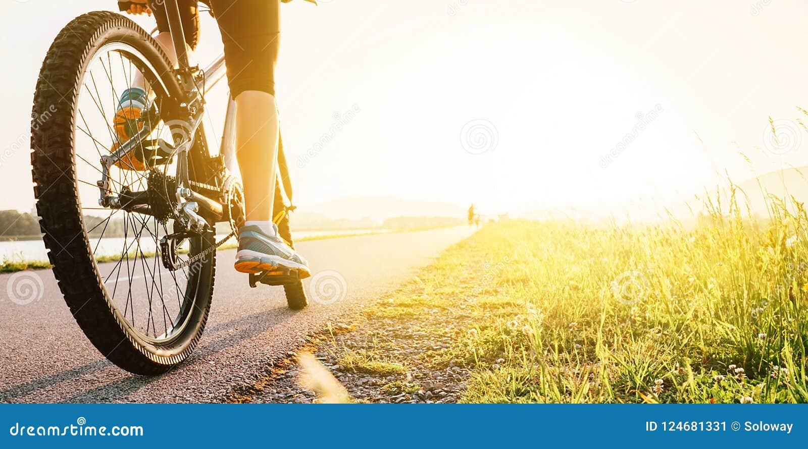 Πόδια γυναικών στο πεντάλι bycikle στο φως ηλιοβασιλέματος